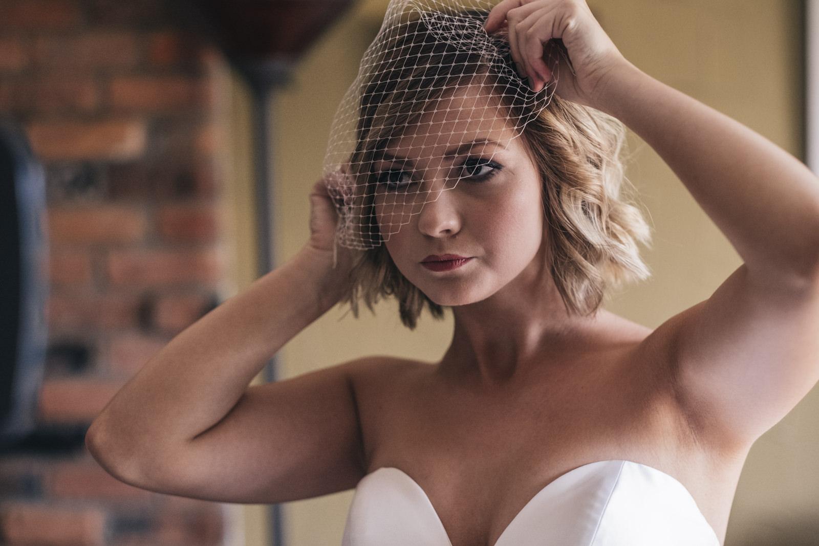 Bride putting on birdcage veil on wedding day.