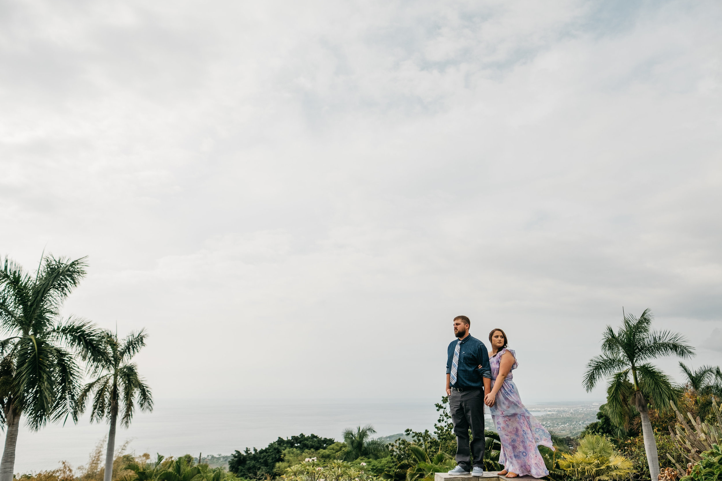 Bride and groom pose for a wedding picture overlooking the beautiful island of Hawaii.