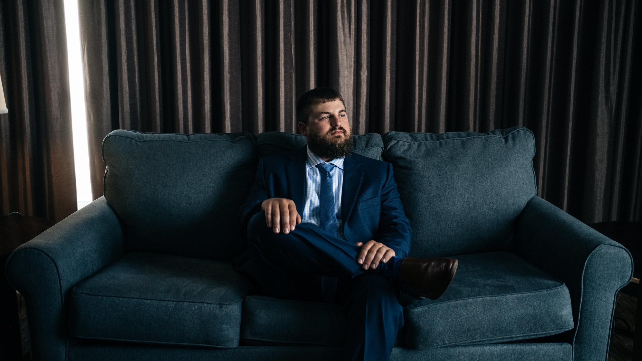 Groom sits on couch before his wedding reception in Toledo, Ohio.