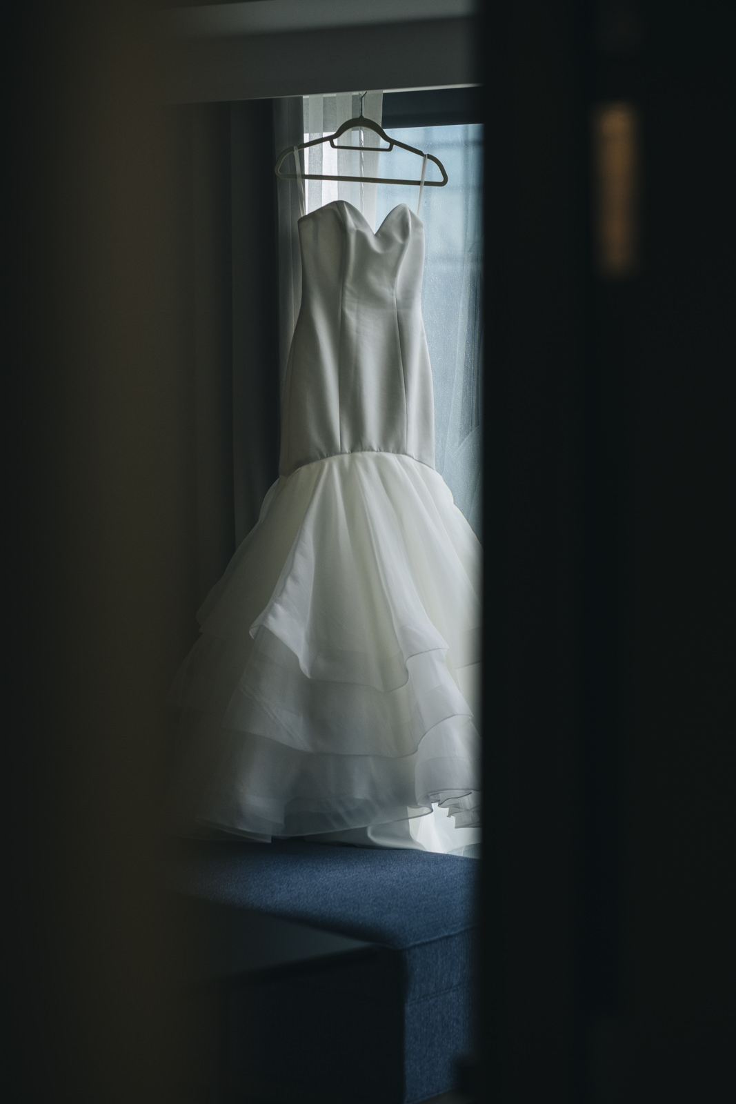 The bride's dress hangs in the window of her hotel suite in Toledo, Ohio.