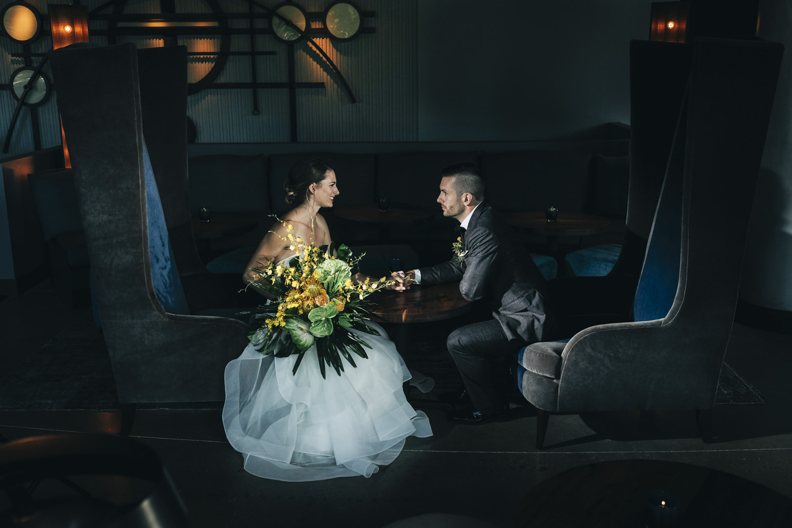 Bride and groom sit in very large chairs at the Renaissance Hotel in Ohio.