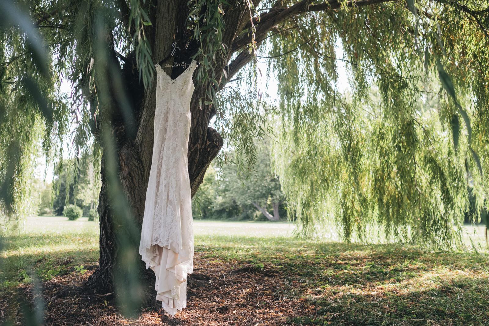 Nautical Pue Michigan wedding dress hanging in a willow tree.