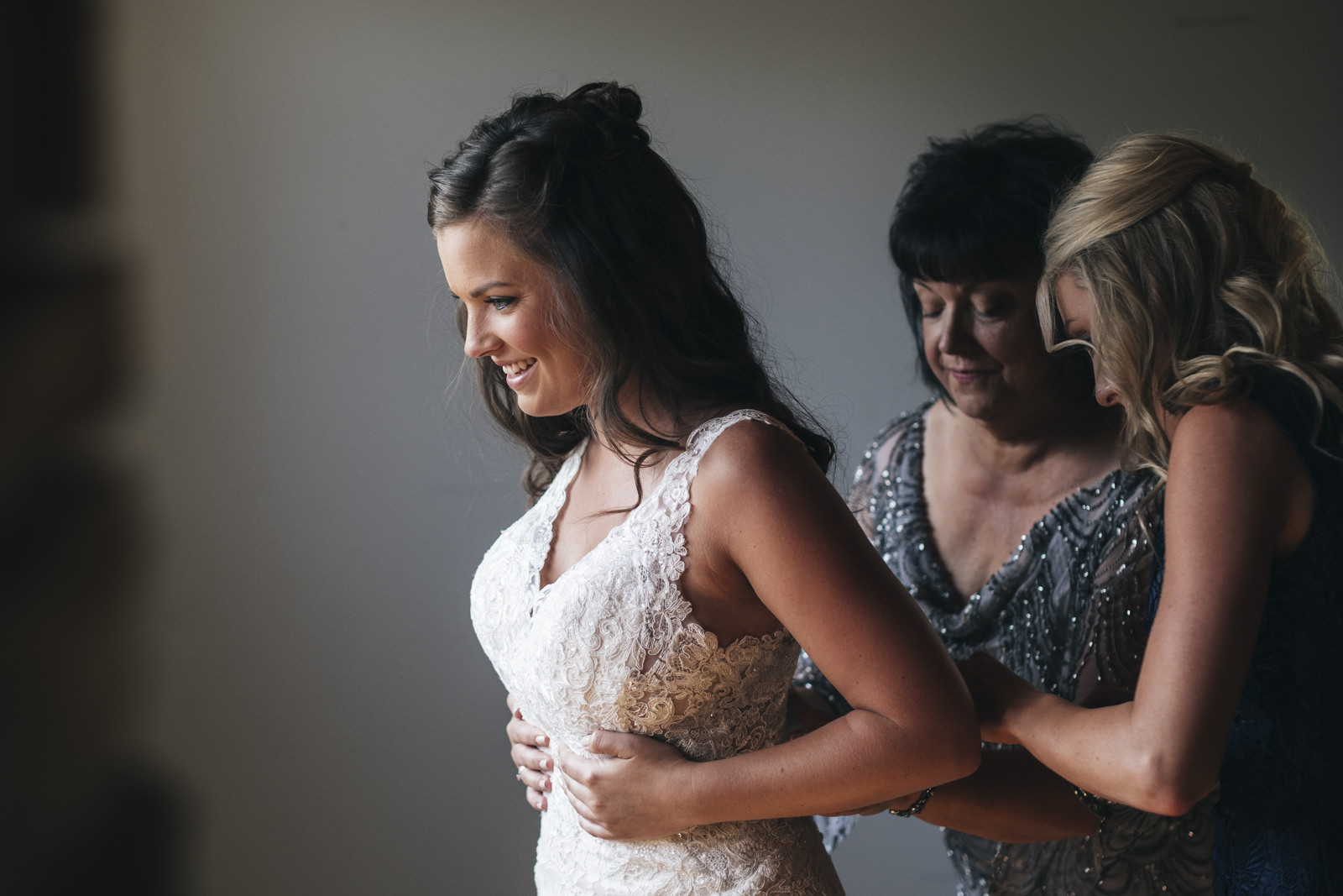 Bride steps into her dress on her wedding day in Pure Michigan.