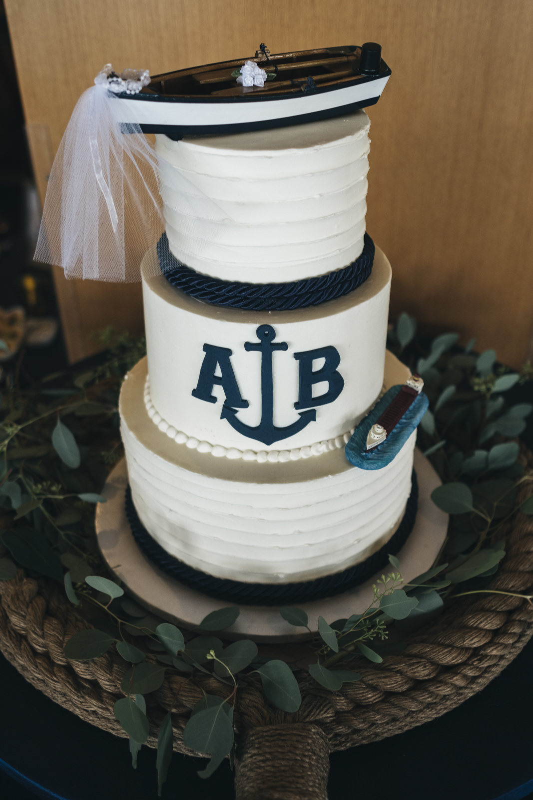 Super cute nautical wedding cake complete with two boats and an anchor.