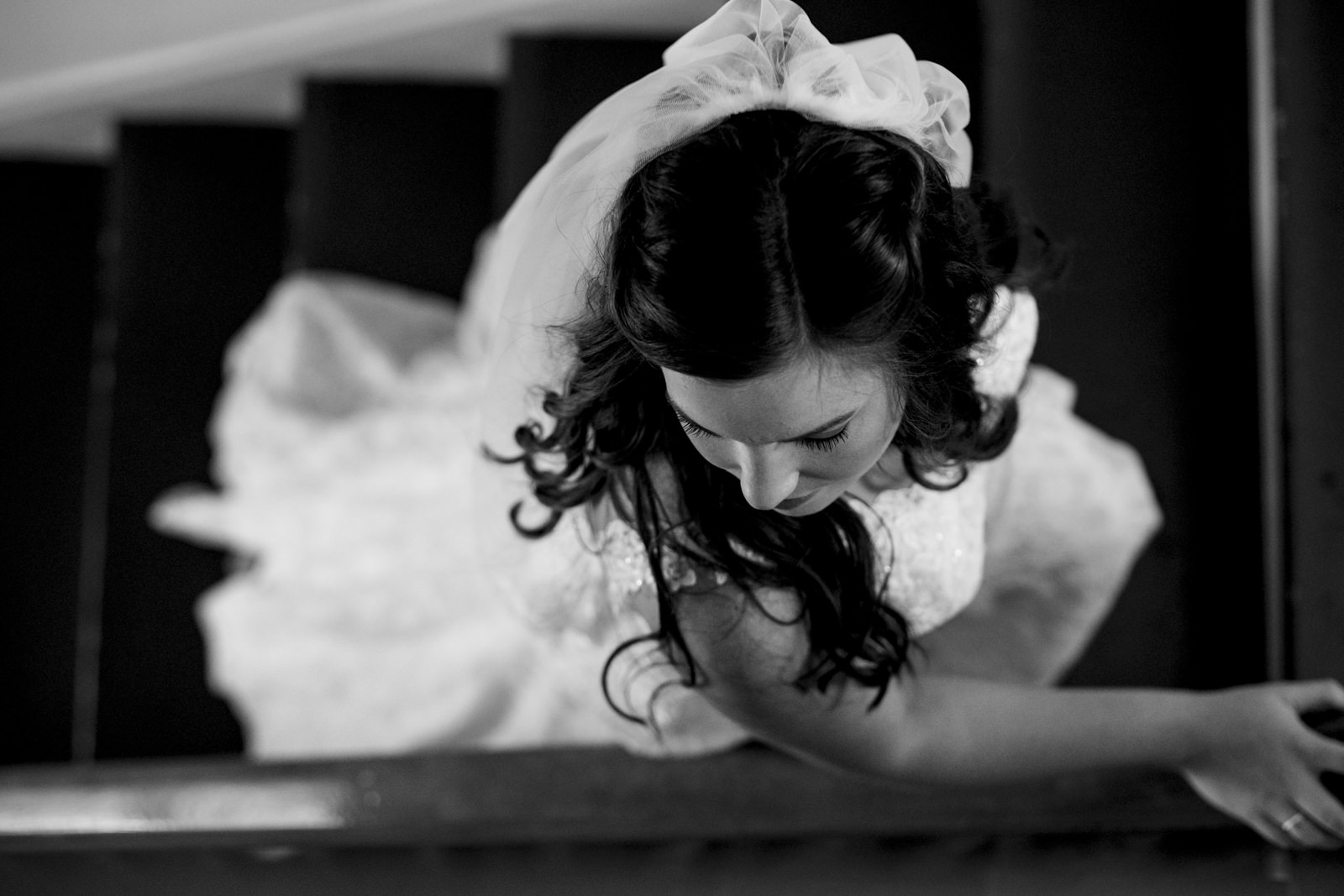 The bride climbs the stairs in her beautiful wedding dress.