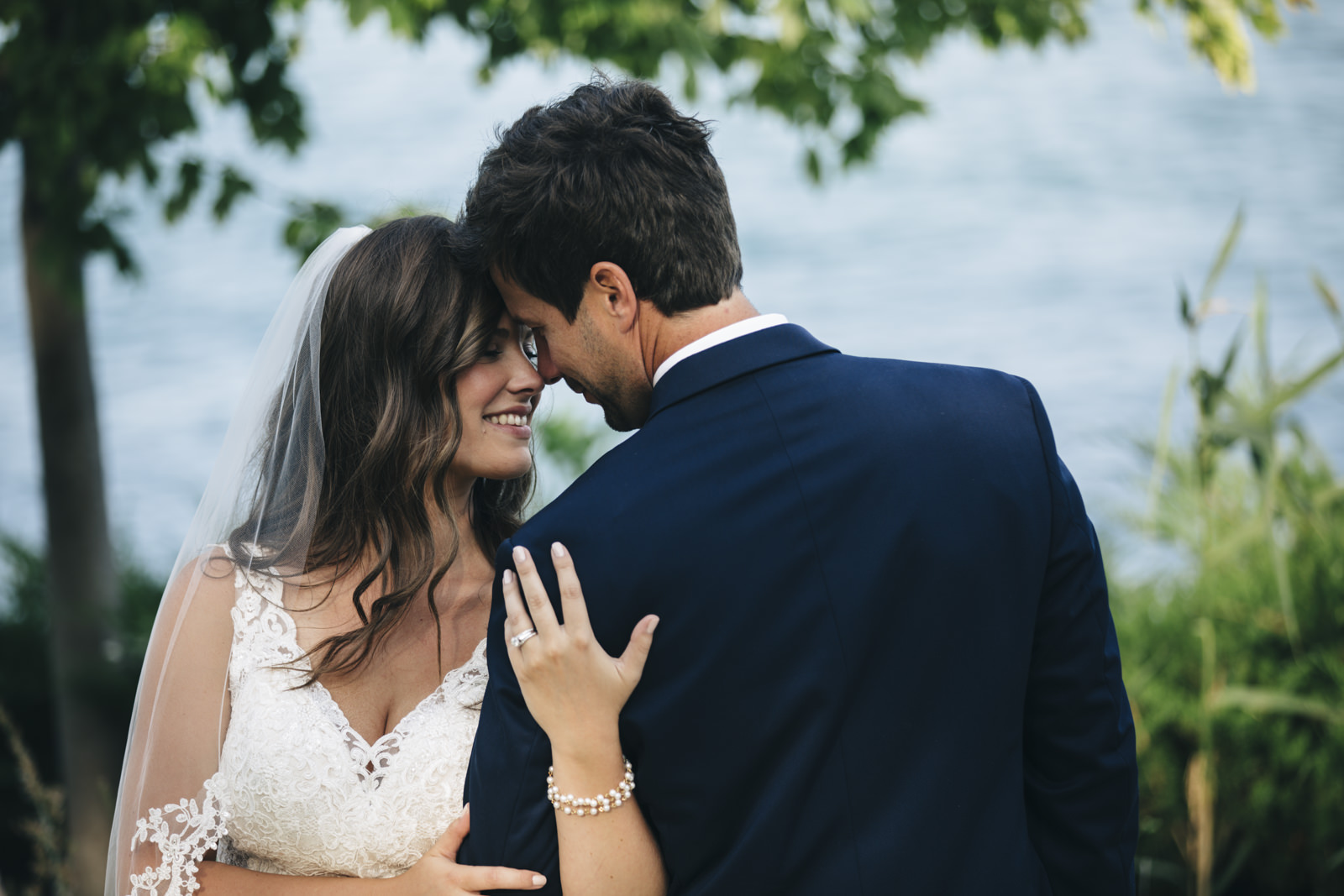 Bride and groom go head to head and smile for a picture near the lake in Michigan.