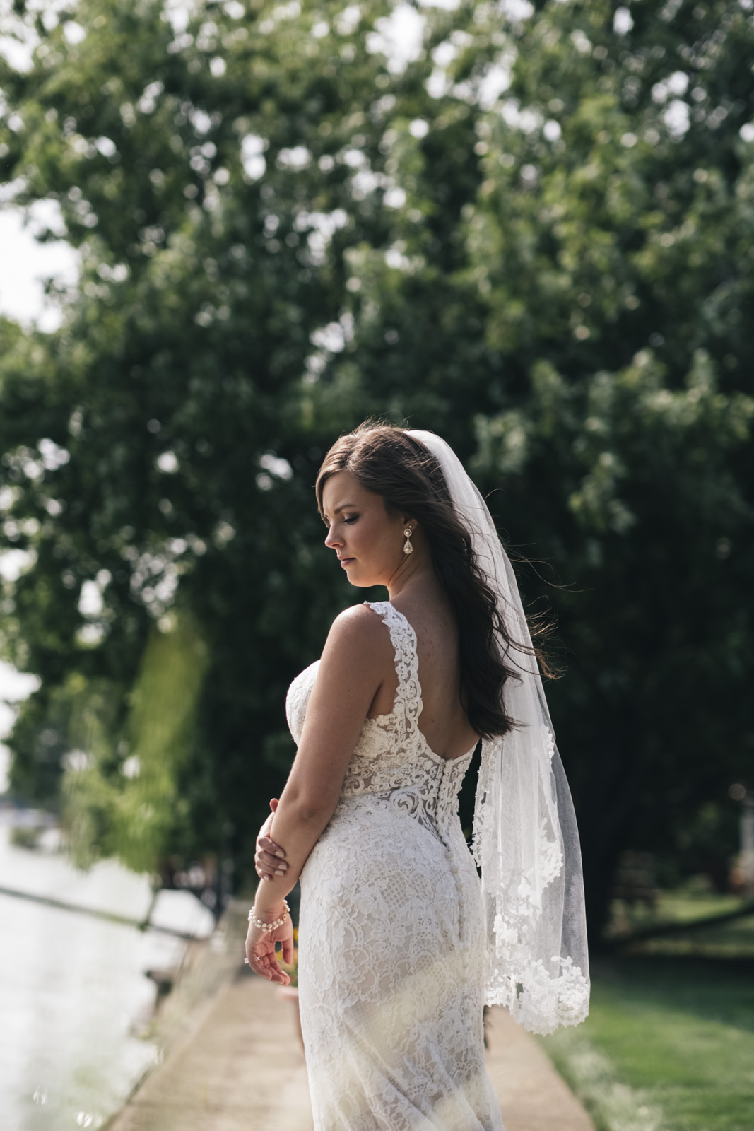The bride poses near the lake for her wedding pictures in Michigan.