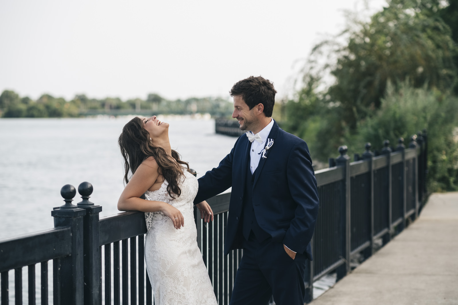 The bride and groom share a laugh near the lake in a relaxed styled session.