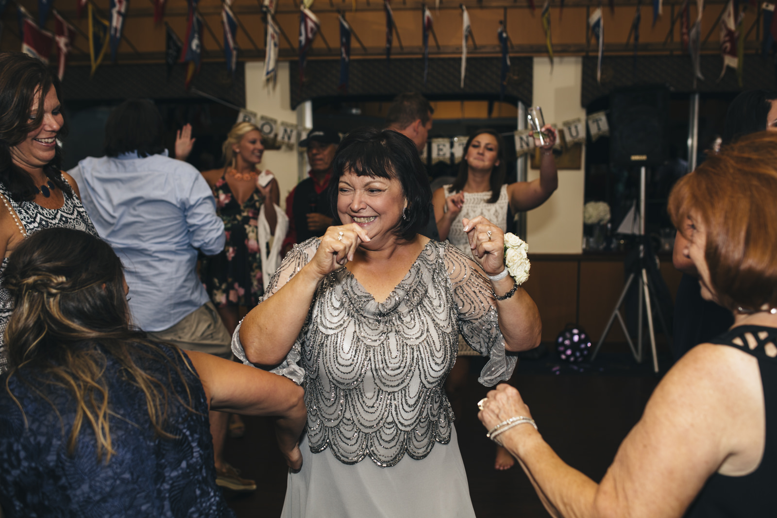 Mother of the brides dances during her daughter's wedding reception.