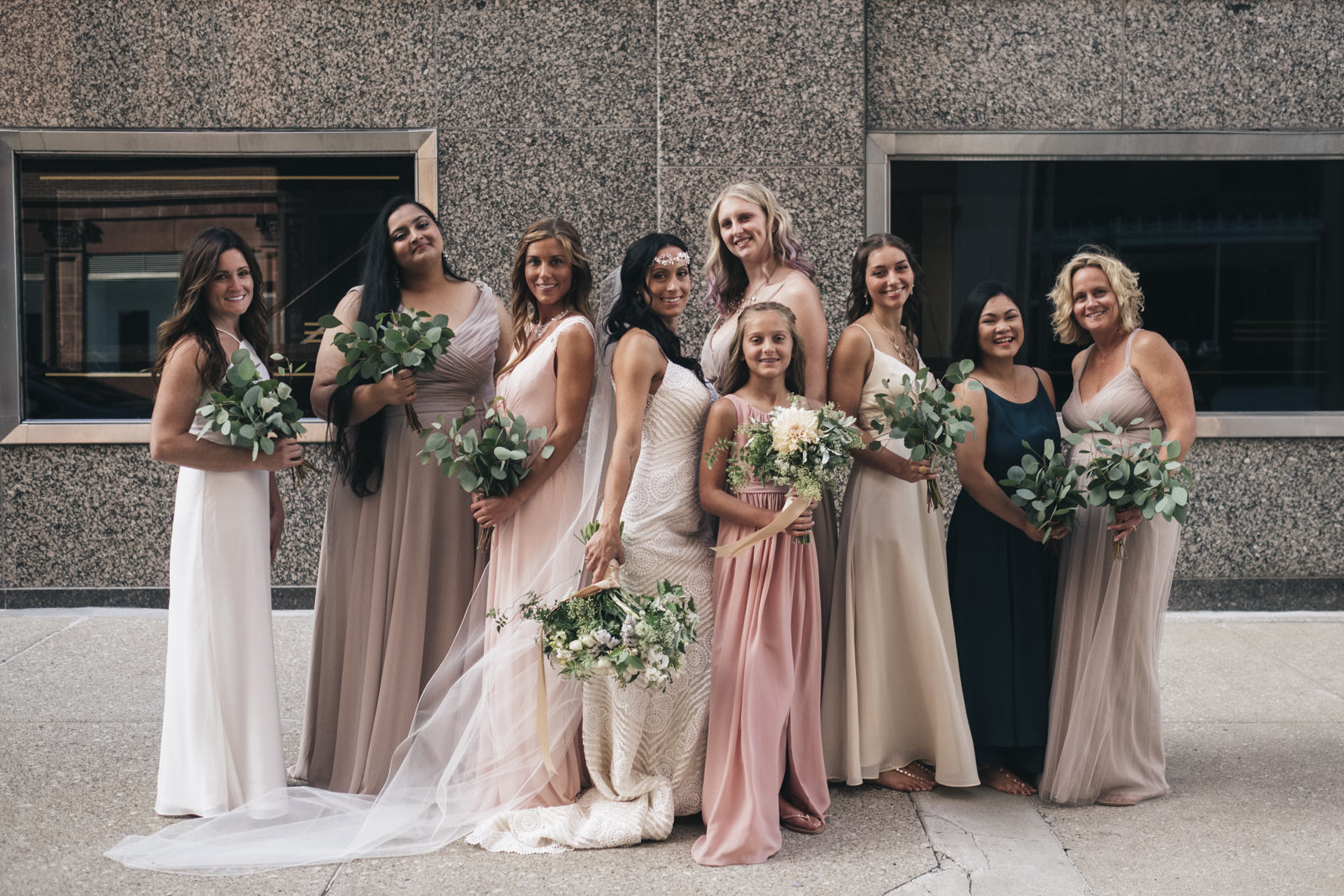 Bridesmaids in neutrals with eucalyptus bouquets in downtown Toledo.