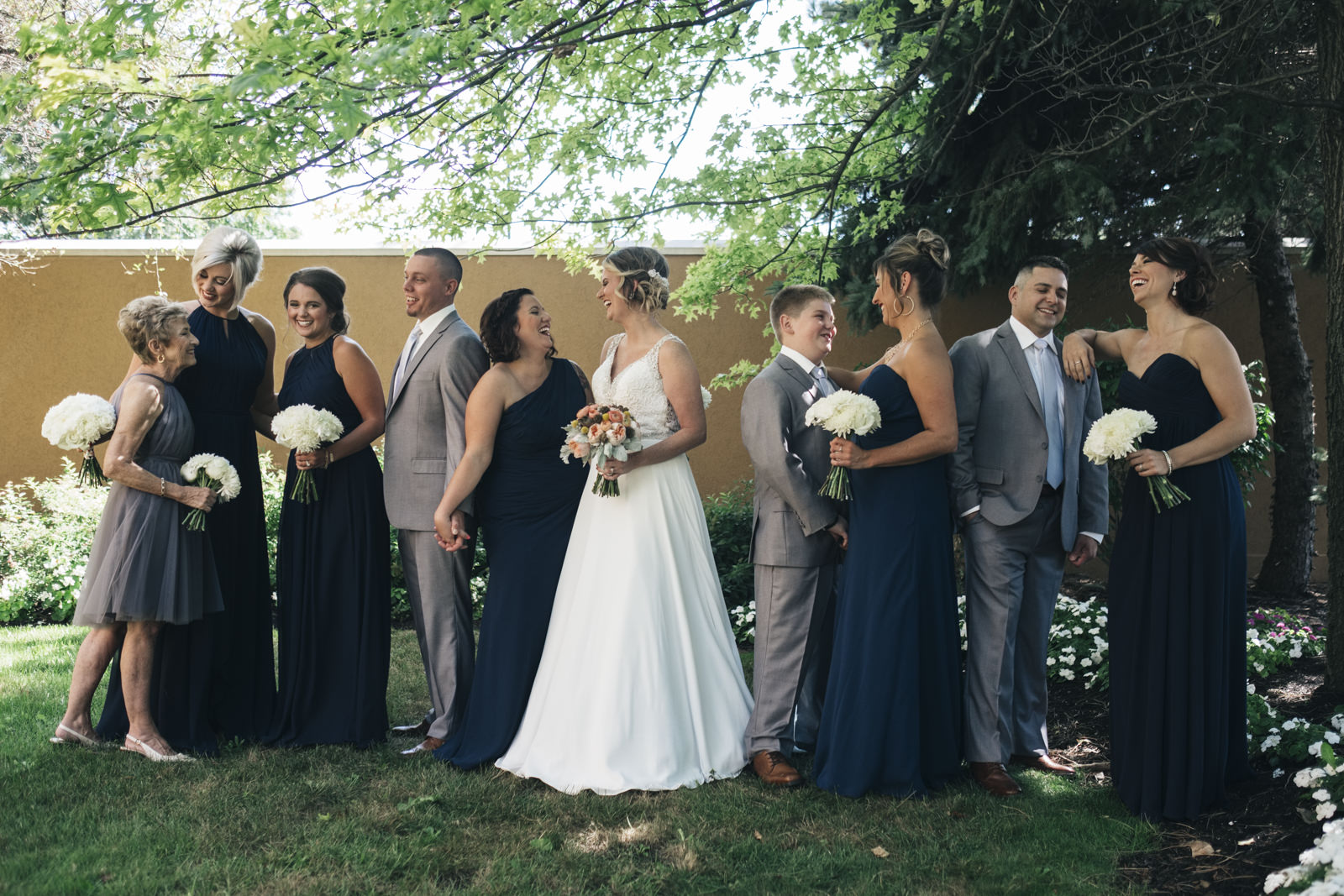 Bridesmaids and men stand around bride before her wedding ceremony in Navy blue dresses and white floral bouquets.