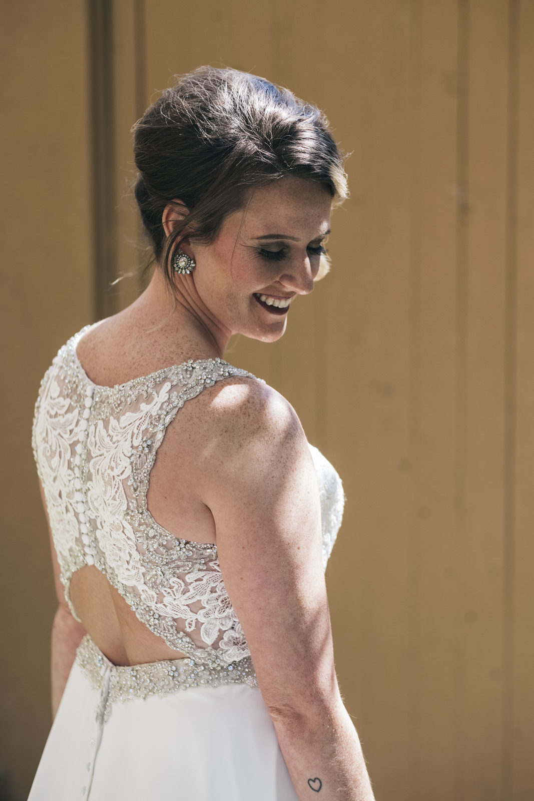 Chris looks over her shoulder and smiles before her wedding ceremony at The Premier in Maumee, Ohio.