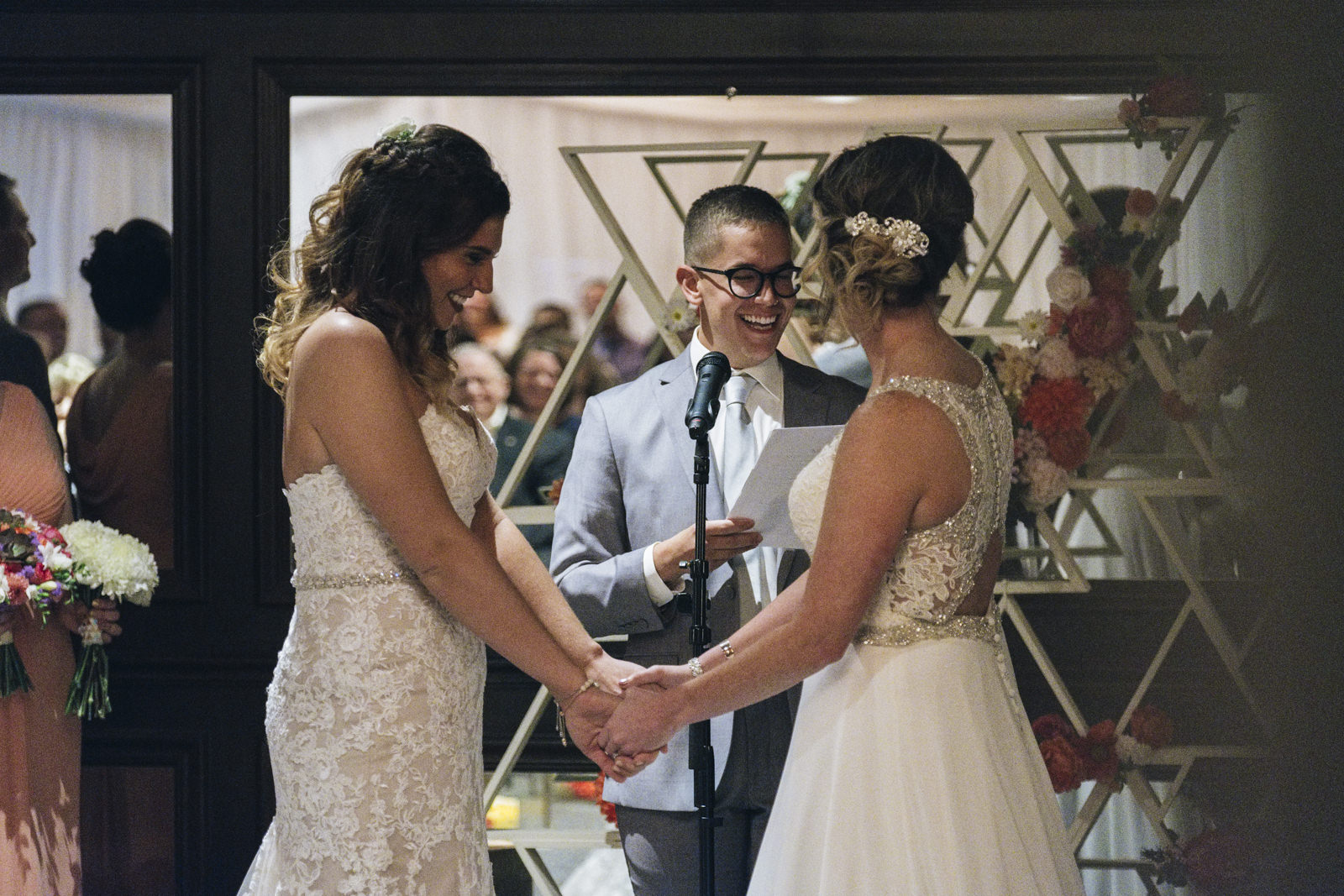 Brides smile and hold hands at the alter for their wedding ceremony in Maumee, Ohio.