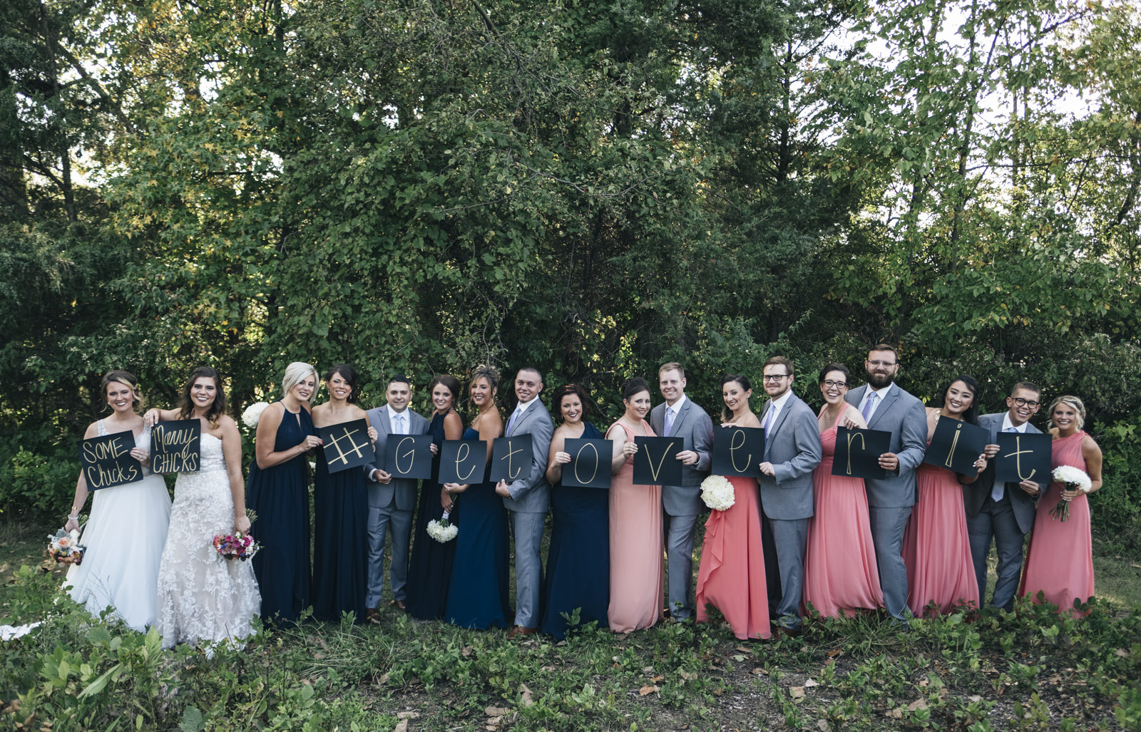 Bridal party holds up signs that say, Some chicks marry chicks, #getoverit for lesbian wedding in northwest Ohio