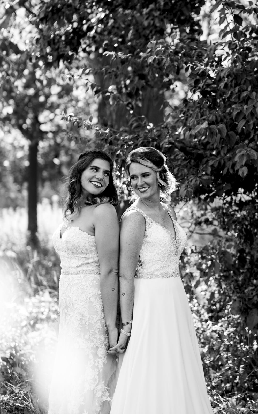 Brides hold hands and show off their matching tattoos at the park in Northwest Ohio