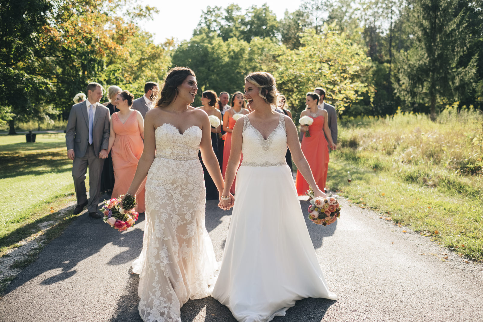 Brides walk down a path with their bridal party during Toledo, Ohio wedding.