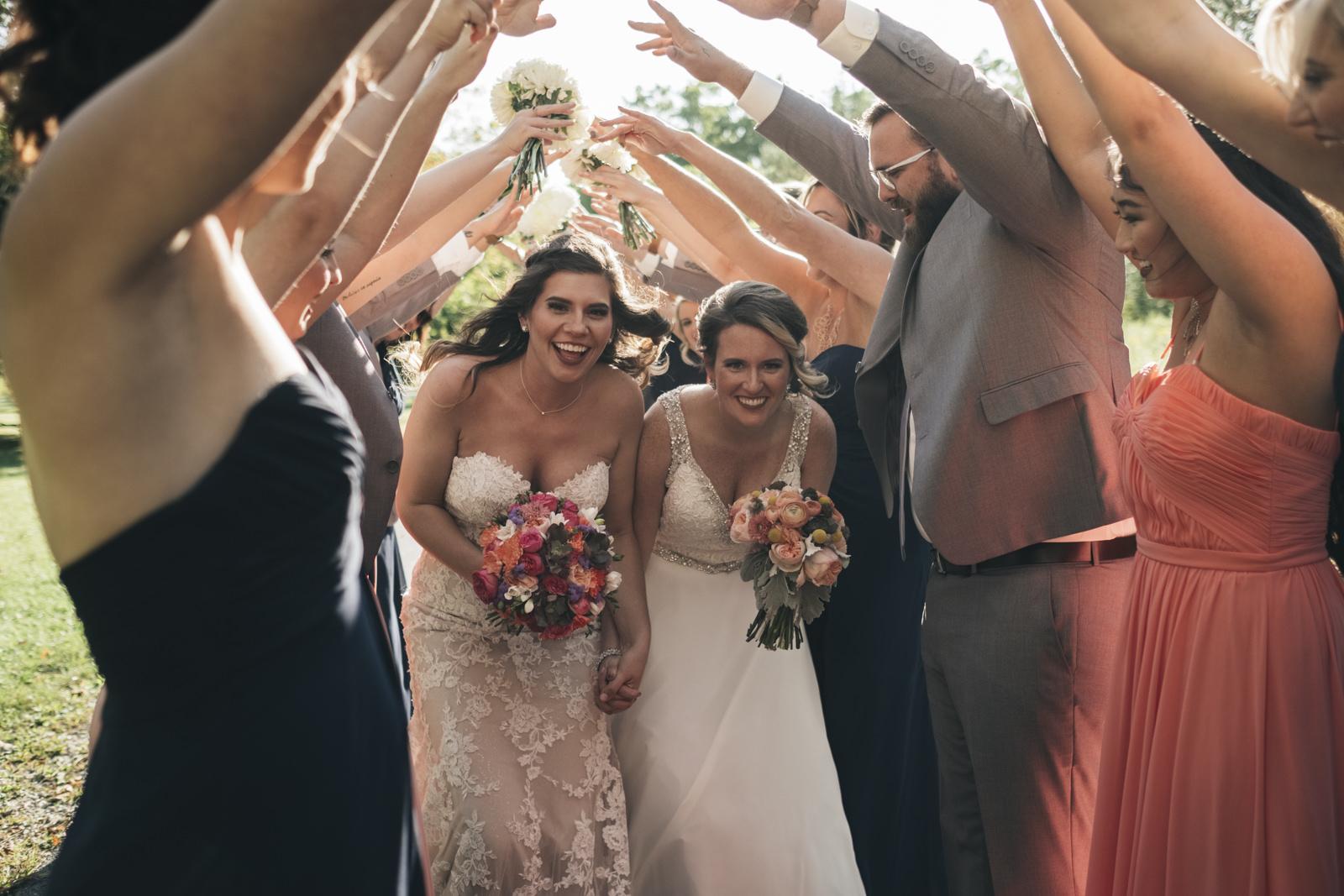 Brides run through a tunnel of their bridal party.