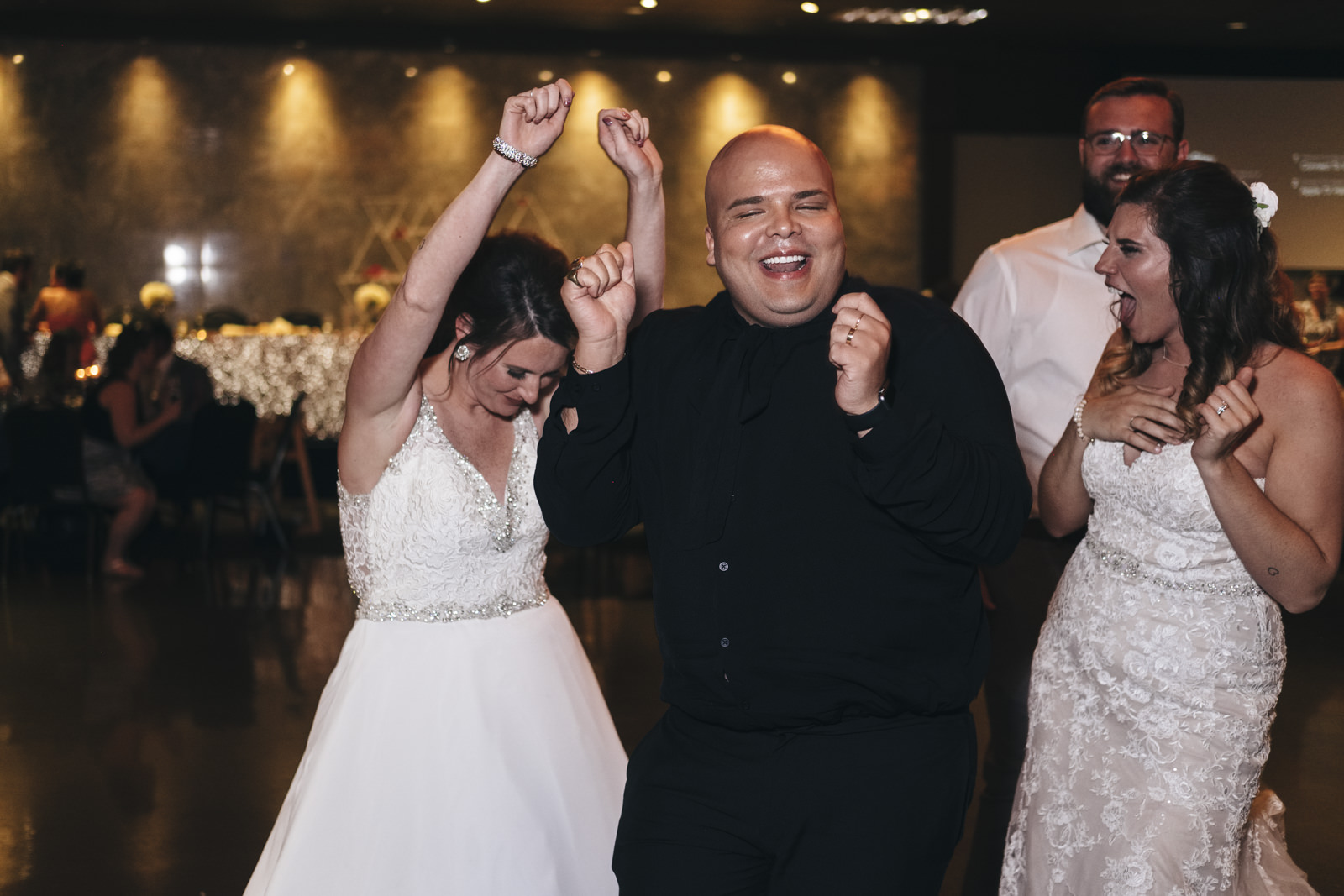 Brides dance with their friends at their wedding reception at The Premier