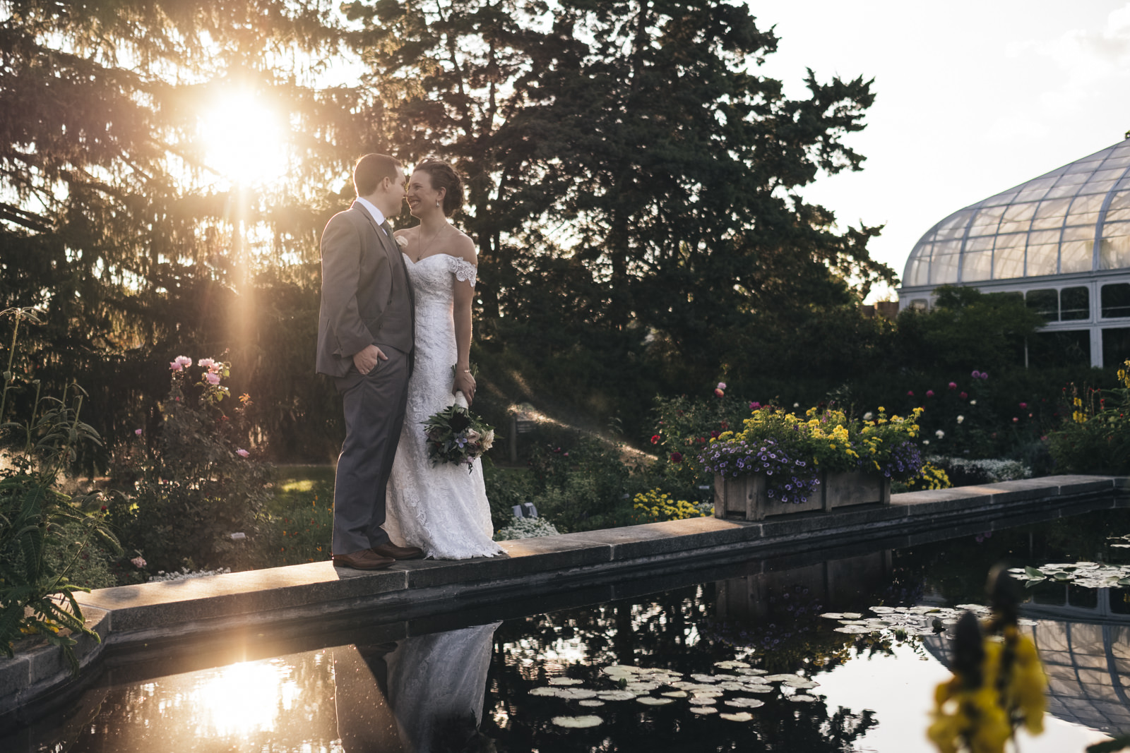 Bride and groom stand on the edge of a pond in the garden at their Toledo, Ohio Zoo wedding.