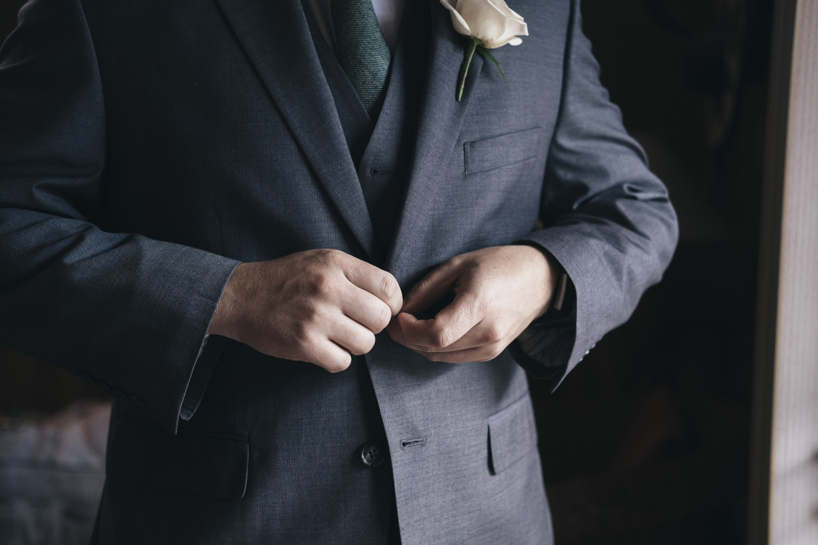 Groom buttons up his suite before his unique wedding ceremony at the Toledo Zoo
