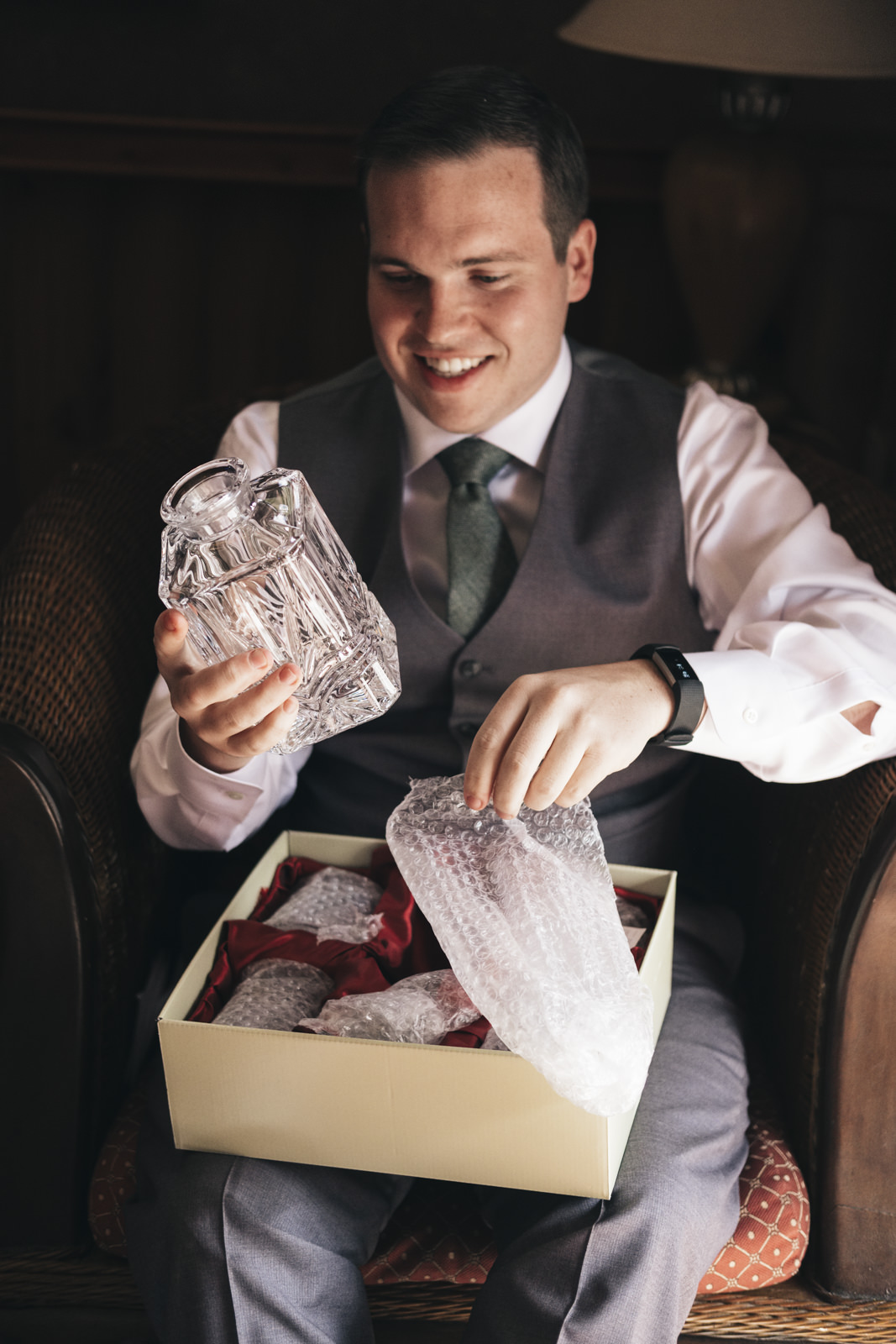 Groom smiles and opens gift from his bride before their wedding ceremony.