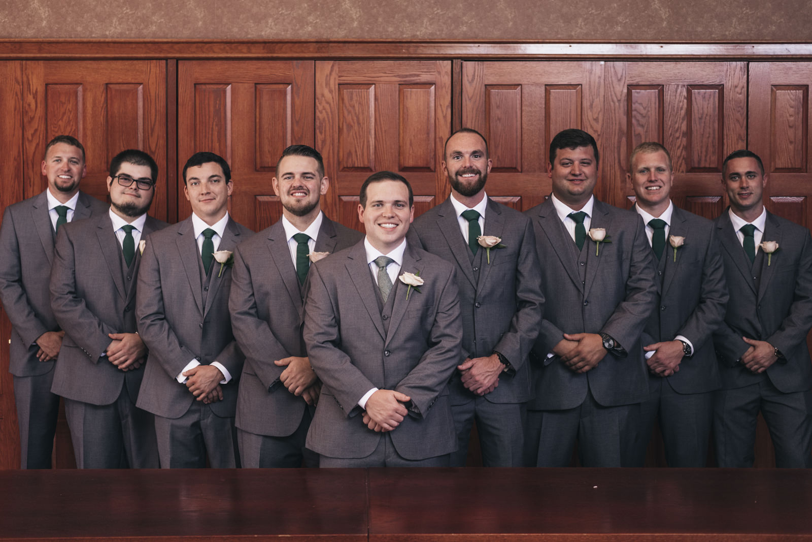 Groomsmen stand at the Toledo Zoo for pictures with the groom before the wedding ceremony