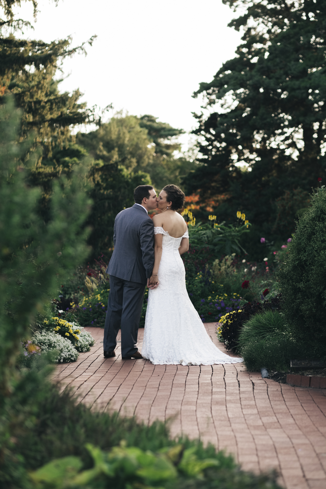 Bride and groom kiss while walking through the garden after their wedding ceremony.