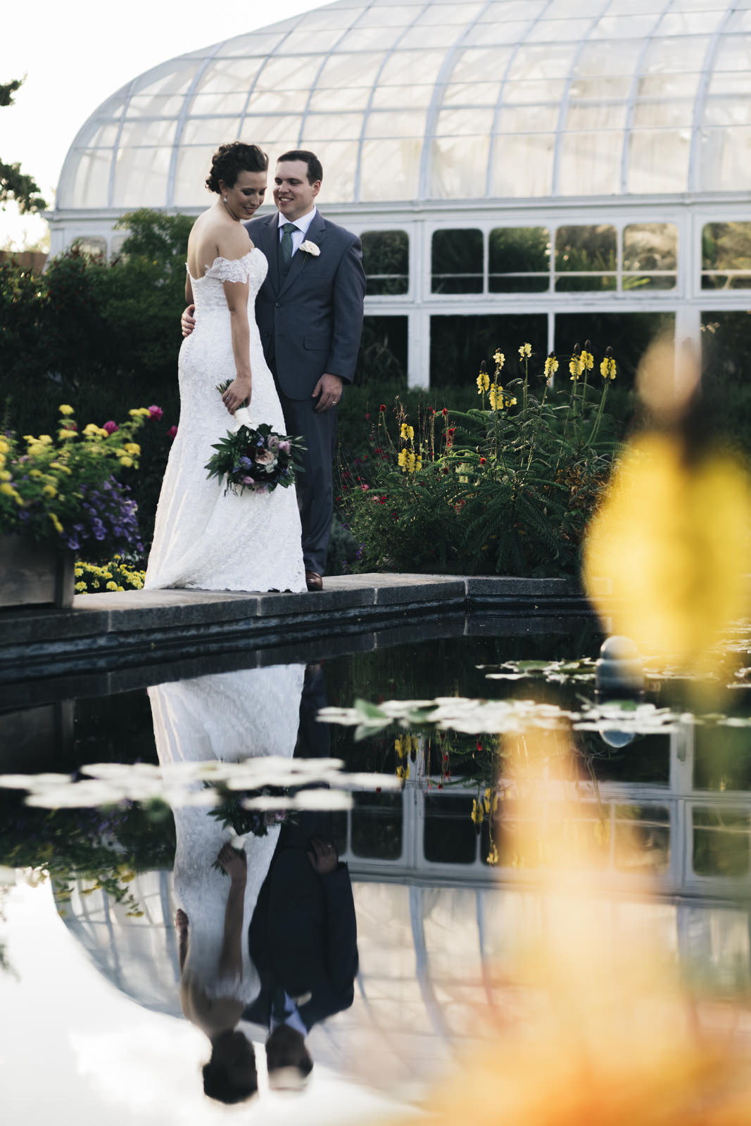 Bride and groom stand on the edge of a pond with their reflection in the water at sunset for their creative session.