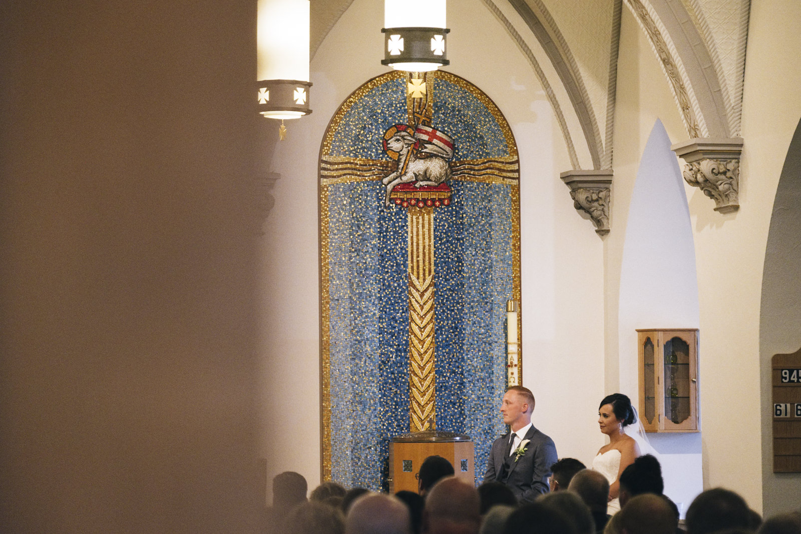 Bride and groom sit and listen to the priest during their Catholic wedding ceremony in Marblehead Ohio