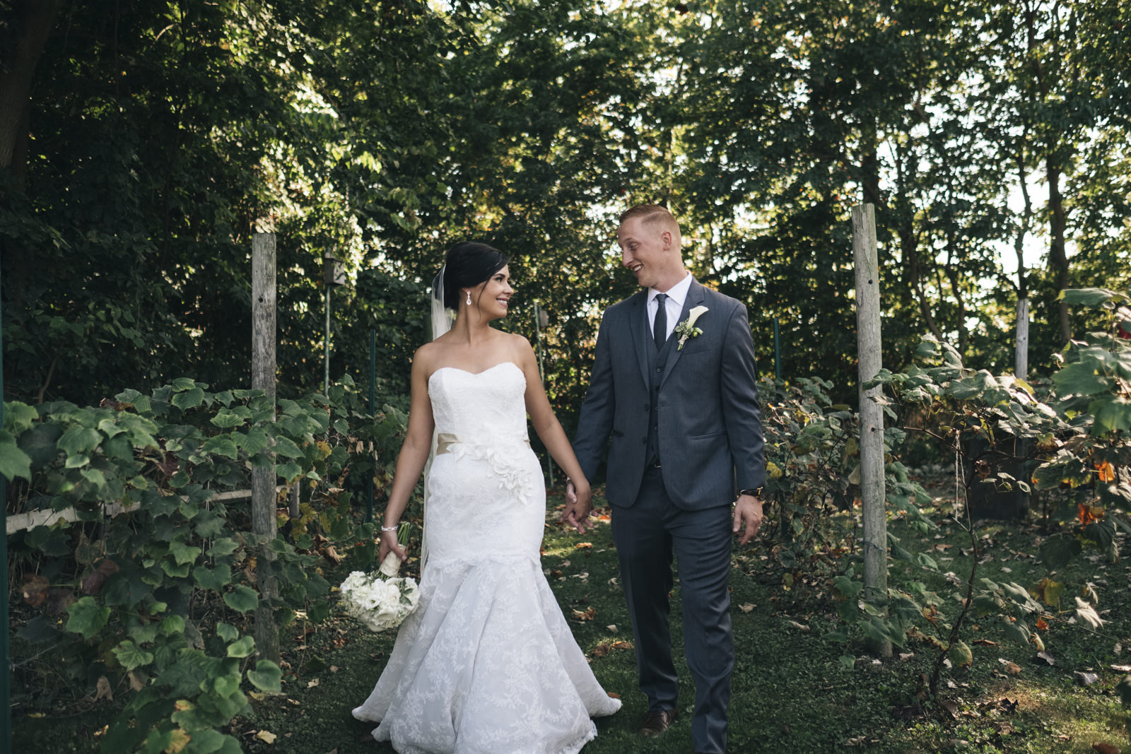 Bride and groom walk down a pathway together after becoming husband and wife in northern Ohio