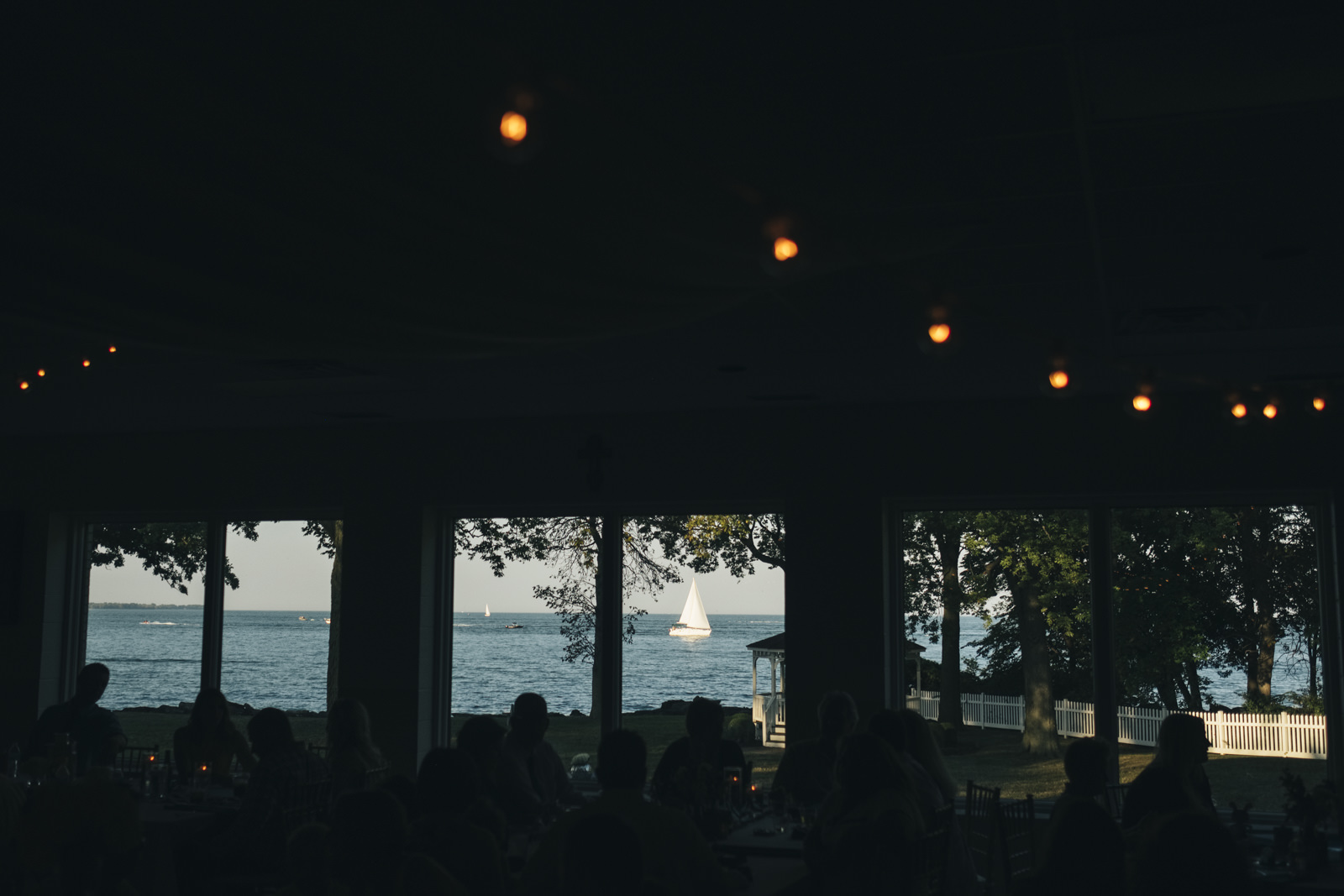A boat sails by a reception venue on Lake Erie