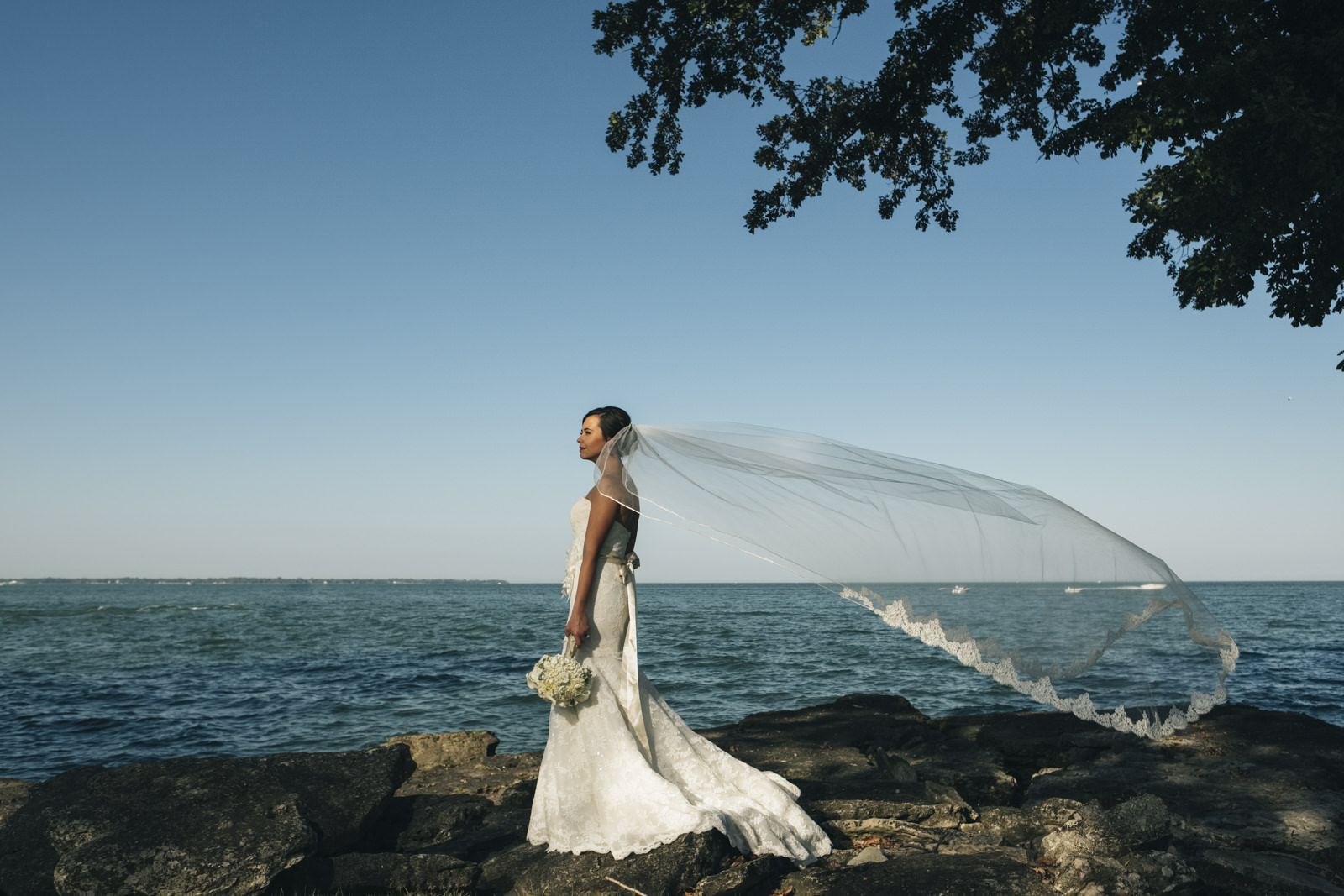 Bride stands near the shore of Lake Erie with her long veil and flowers from Bailey's Buds n Blooms.