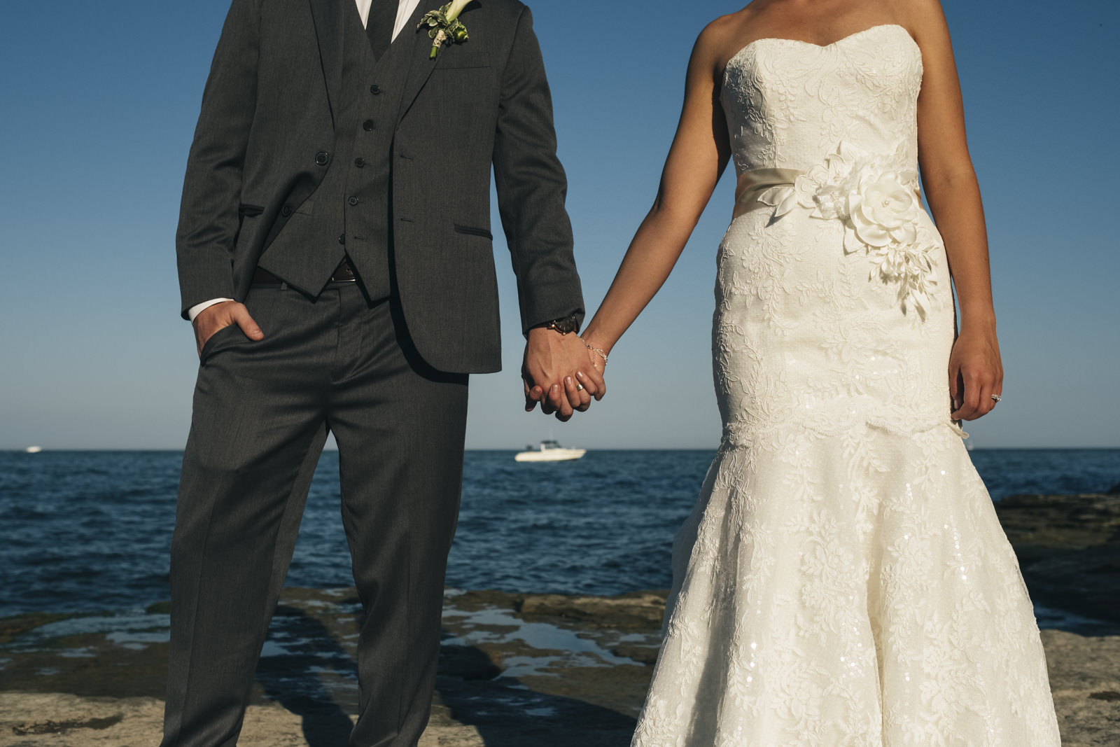 Bride and groom hold hands on the shores of Lake Erie in Ohio