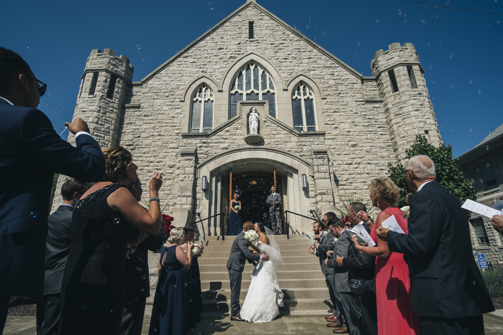 Bride and groom kiss outside of St. Mary's Catholic Church in Marblehead Ohio on their wedding day