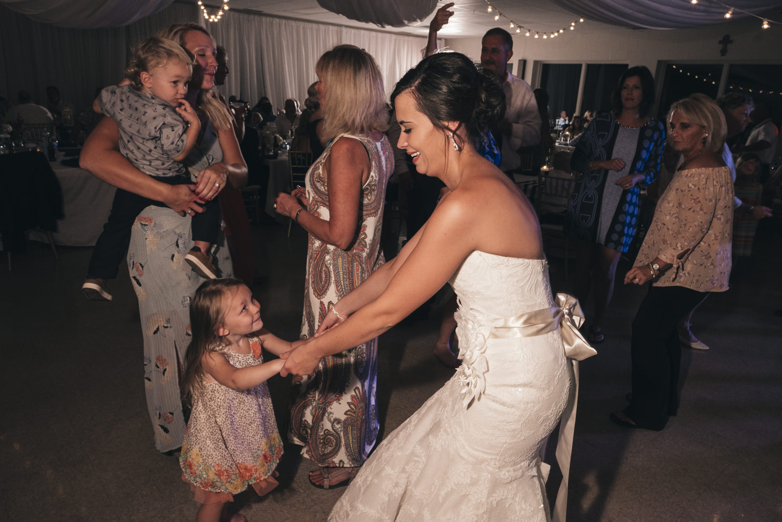 bride dances with a little girl during her wedding reception