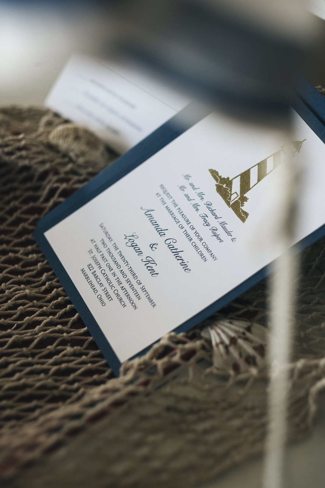 Wedding invitations that are nautical themed with a lighthouse on them.