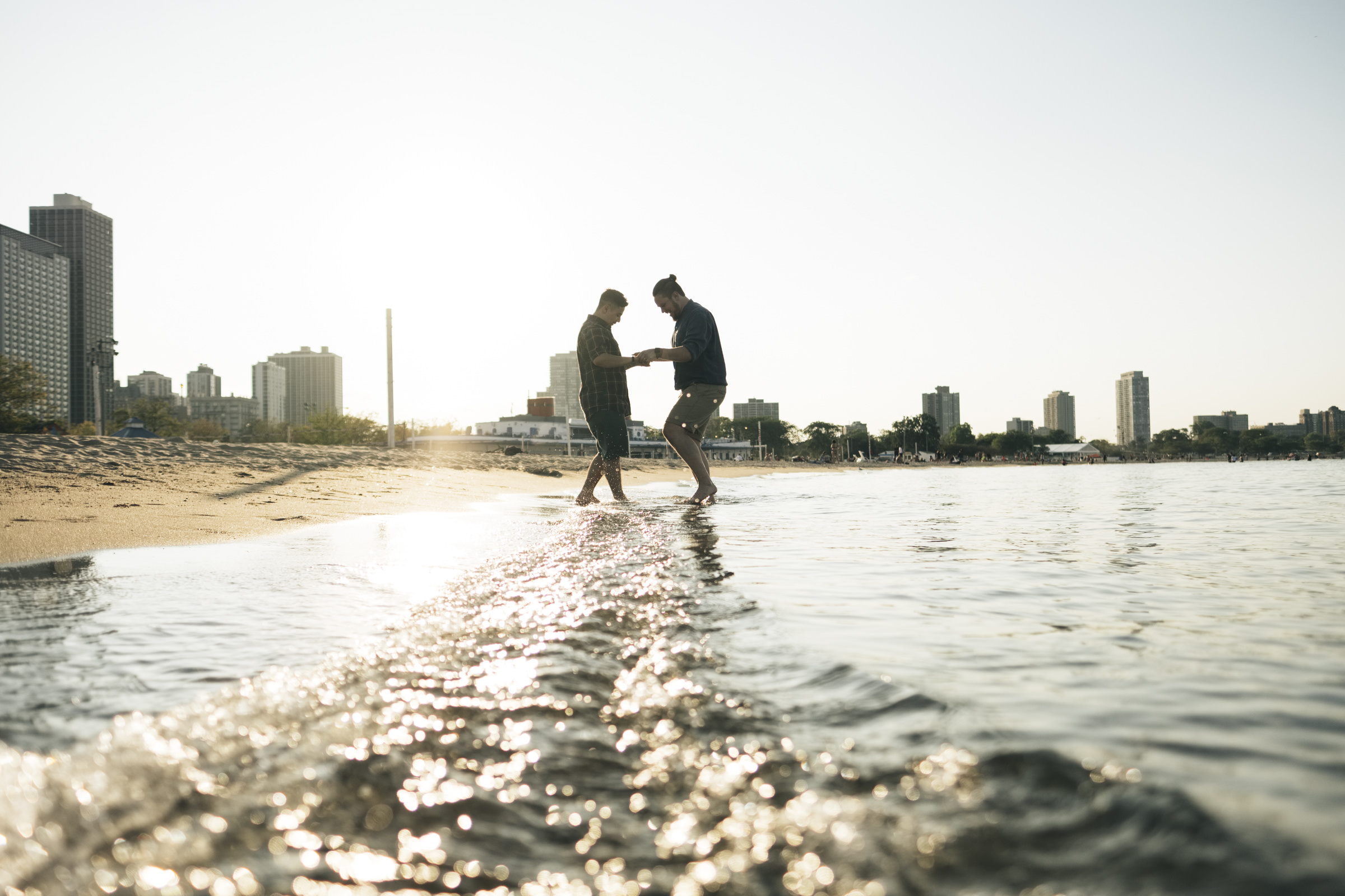 Gay couple dances in the water during their engagement session in Chicago