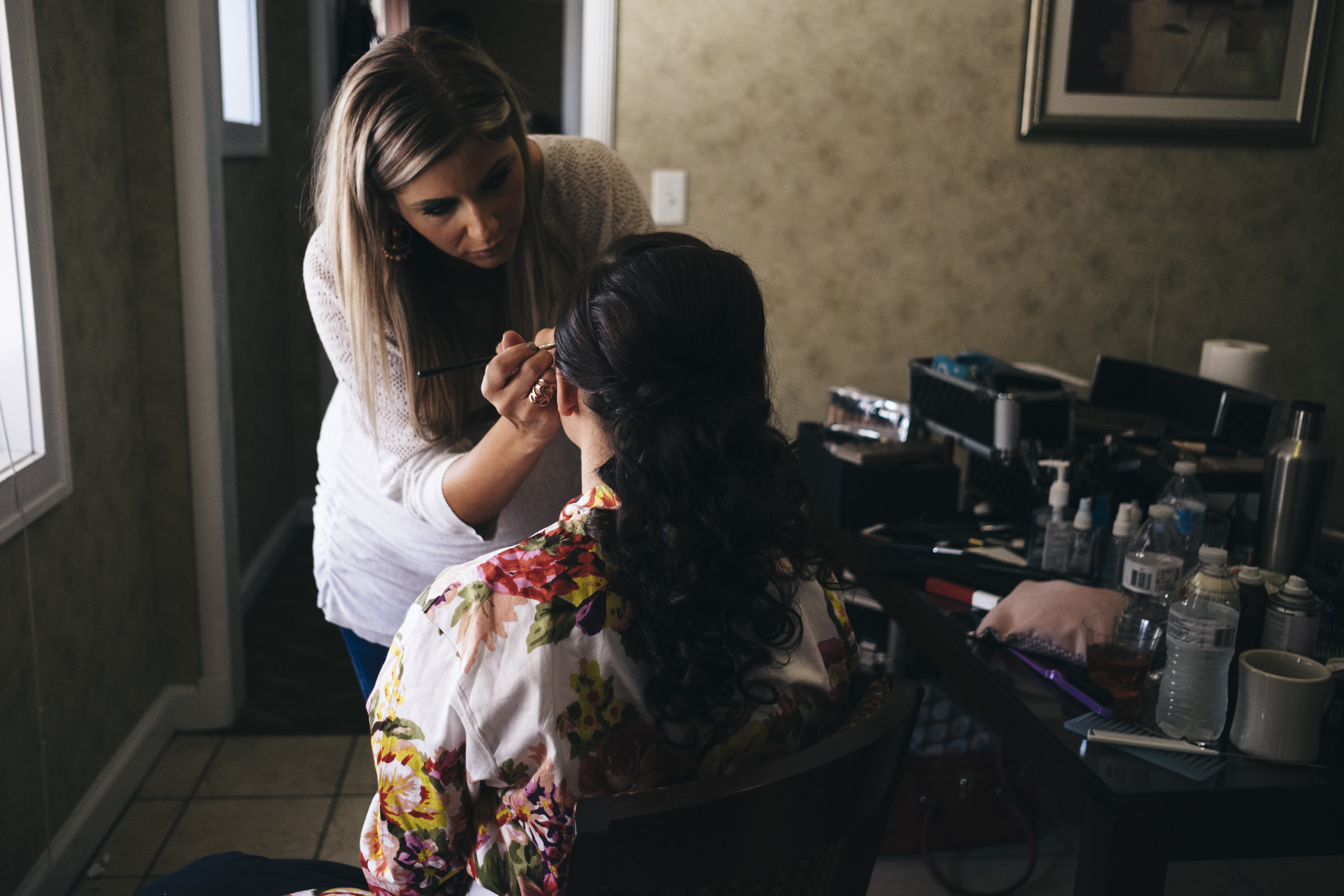 Bride gets her makeup done by makeup artist before her wedding in Port Clinton