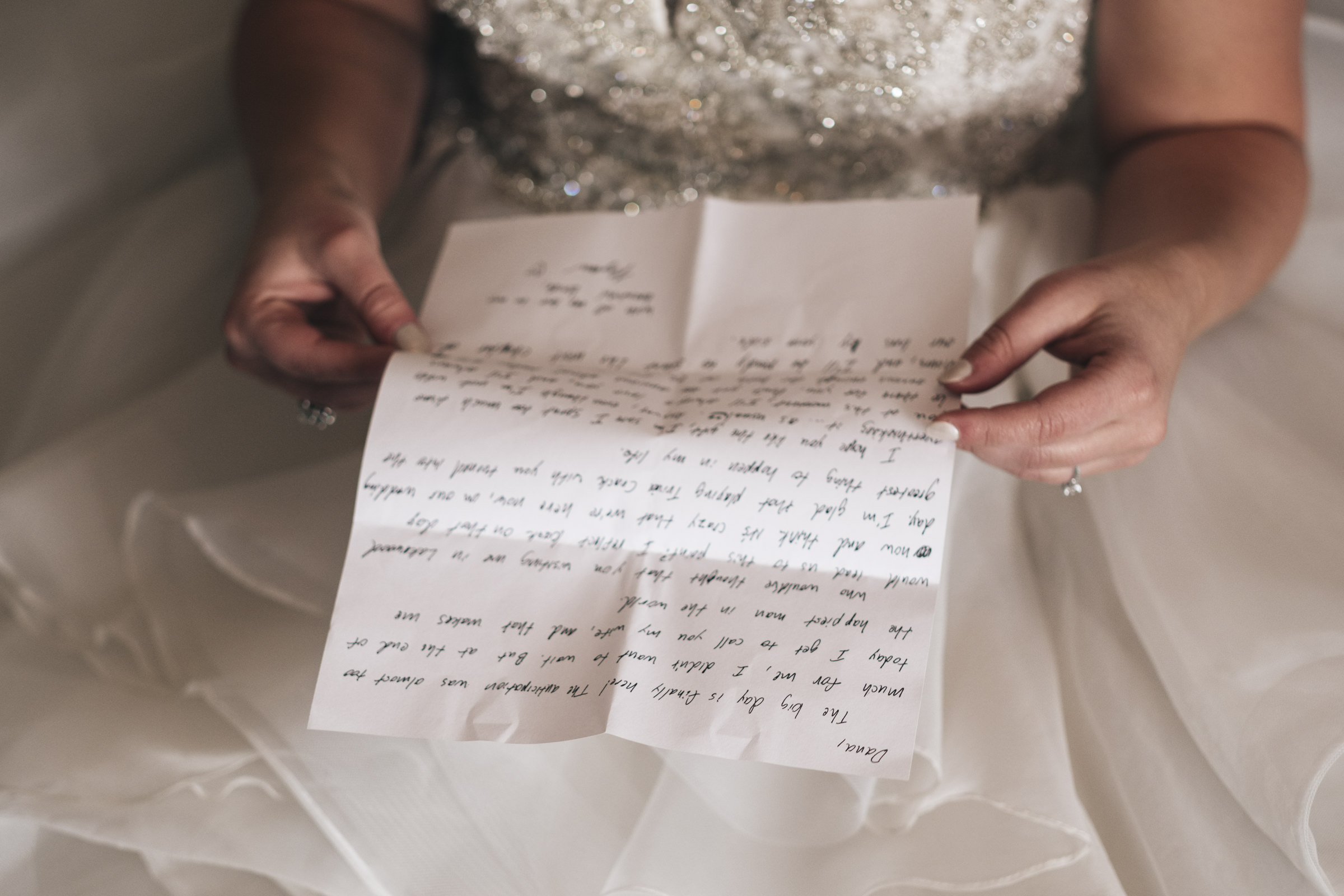 Bride reads a handwritten note from her groom before their wedding ceremony in her hotel room near Lake Erie