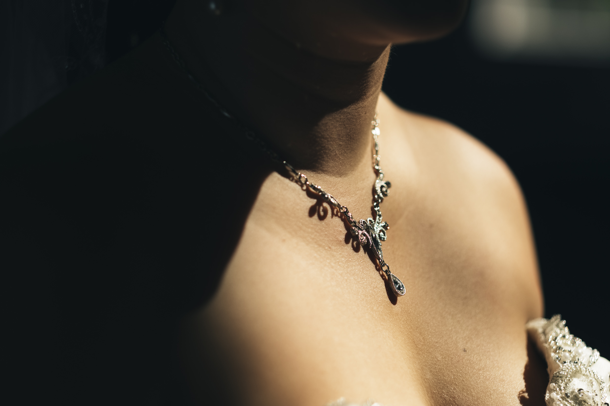 Detail photo of the bride's necklace as she stands in the warm sunlight