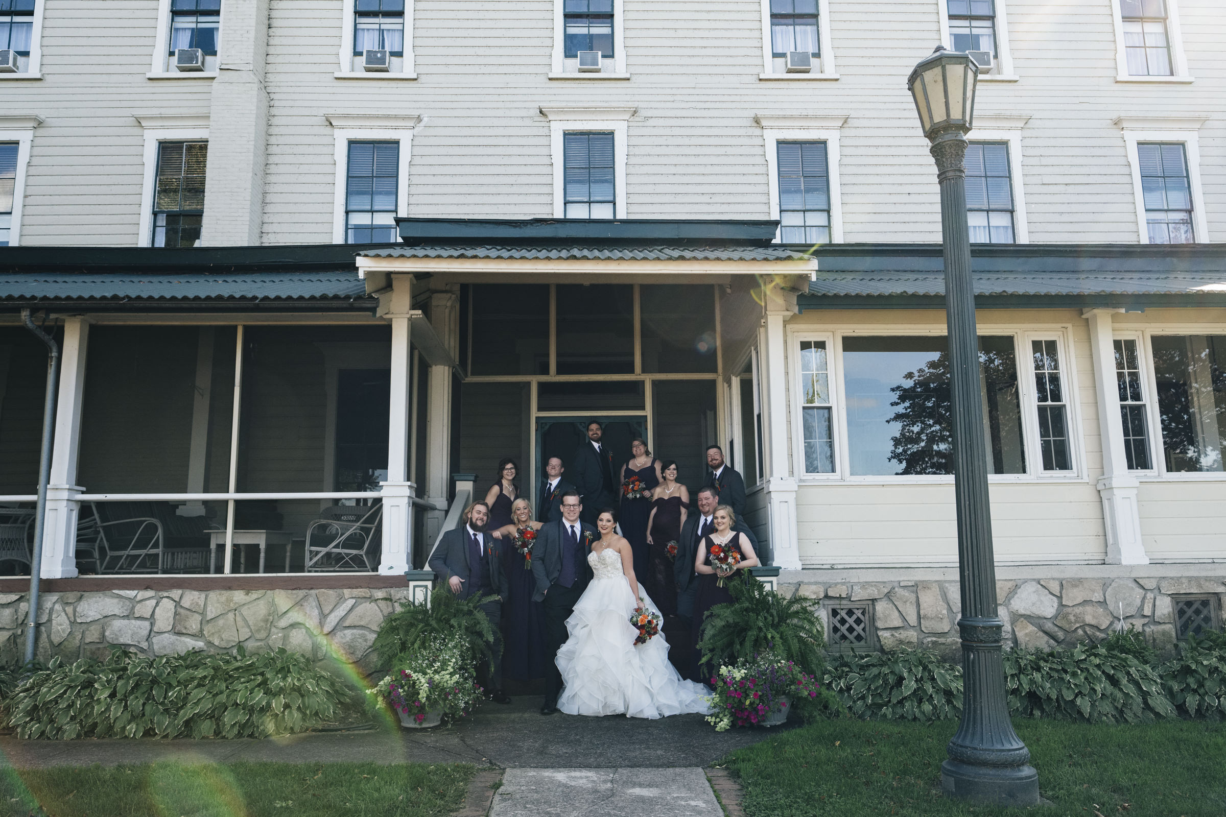 Bridal party stands on the stairs of hotel in Port Clinton wedding