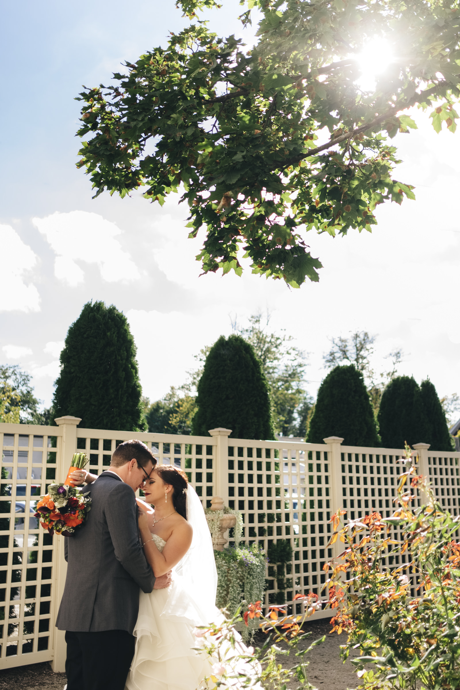 Bride and groom stand in a garden outside of hotel near Lake Erie