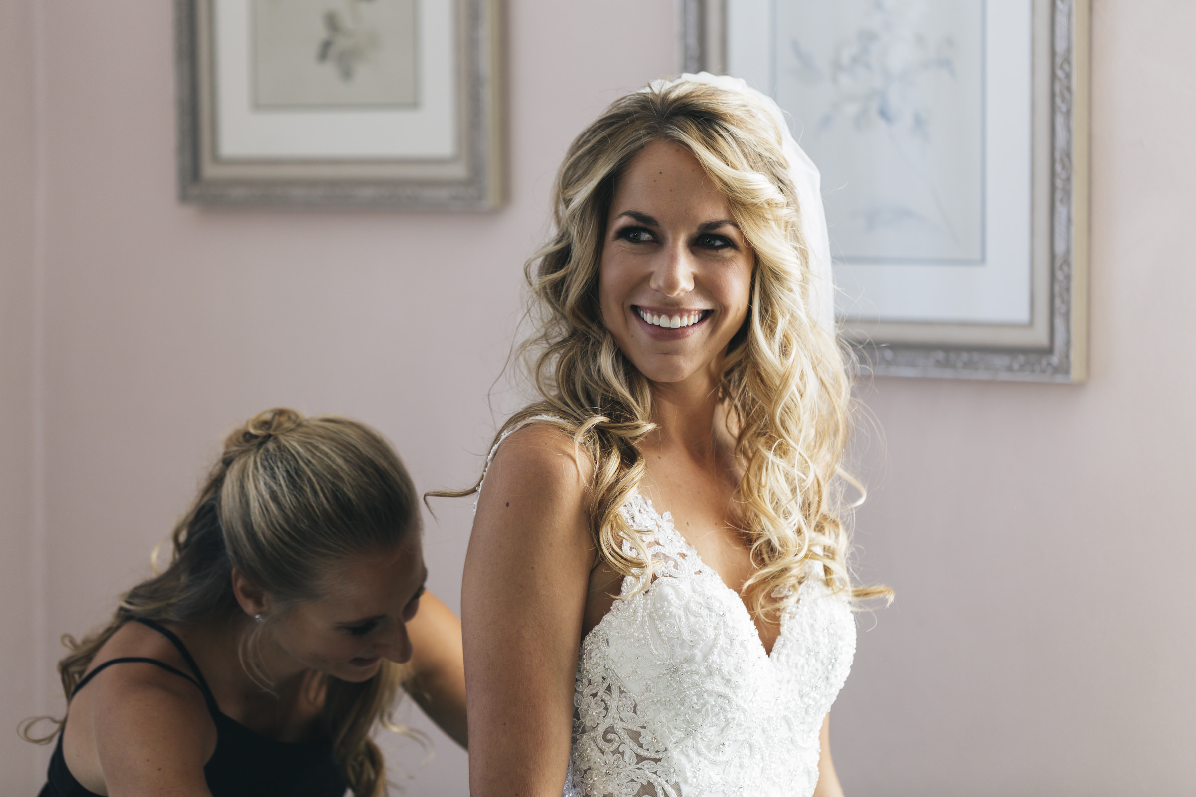 Bride smiles while she gets into her dress before her wedding ceremony in Toledo, Ohio