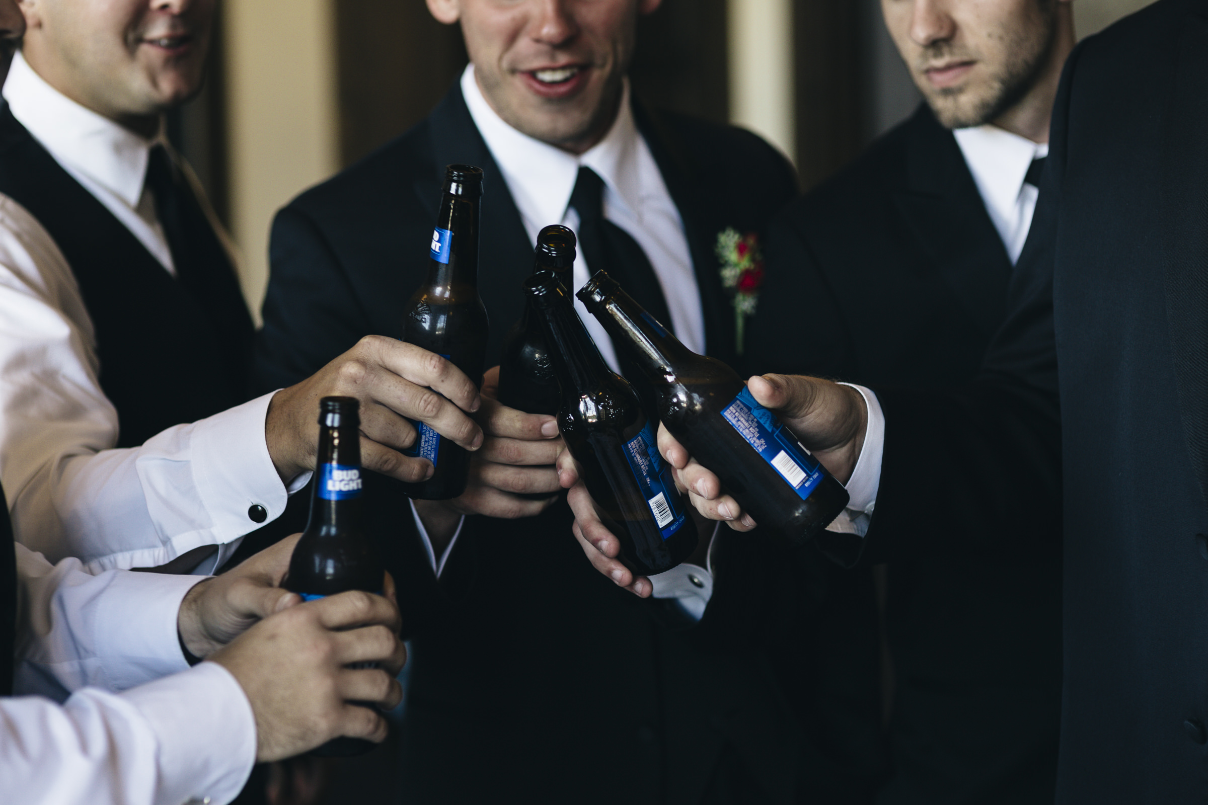 The groomsmen drink a beer before wedding ceremony at Nazareth Hall
