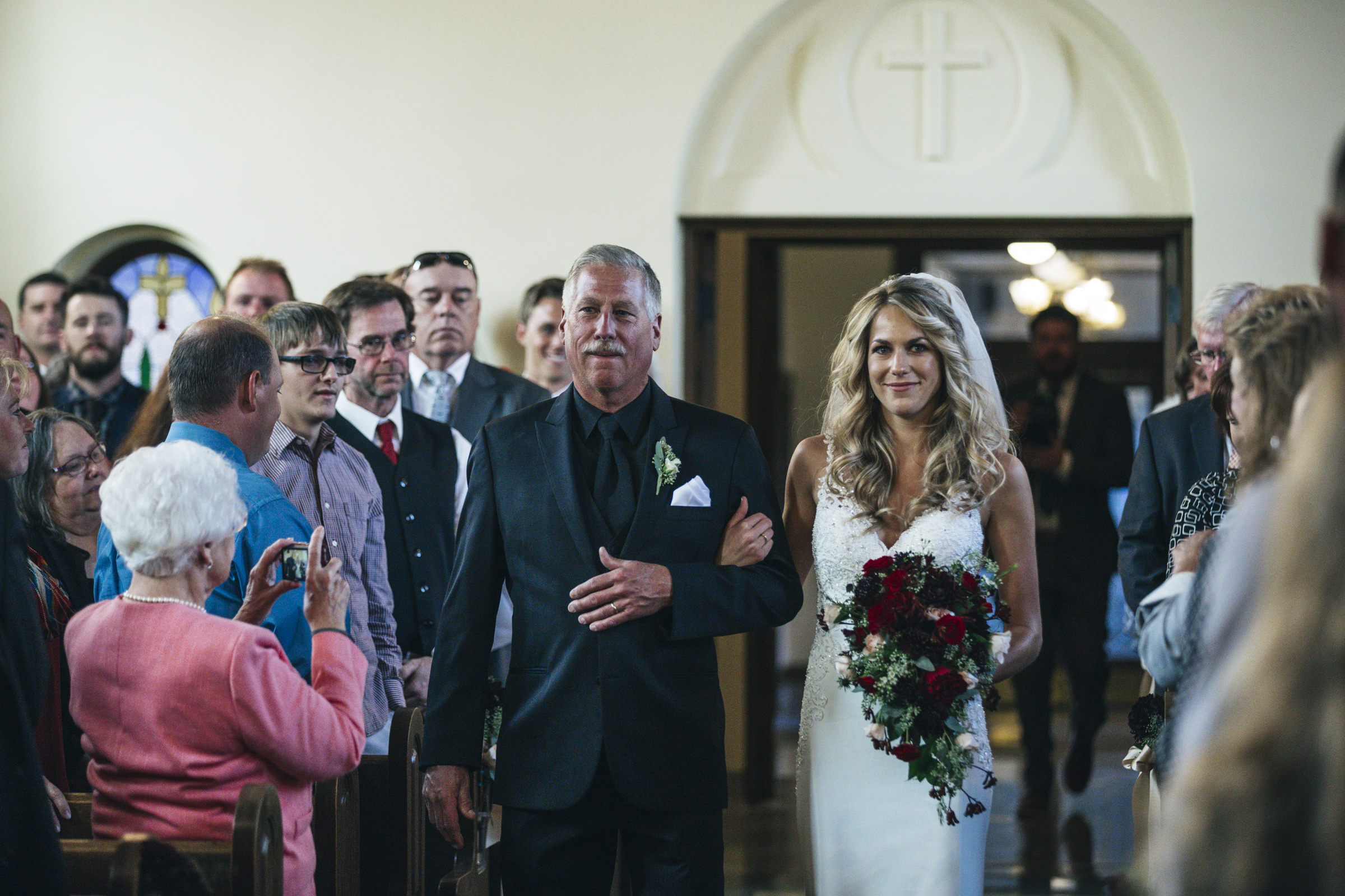 Father walks his daughter down the aisle at her wedding ceremony in Grand Rapids, Ohio