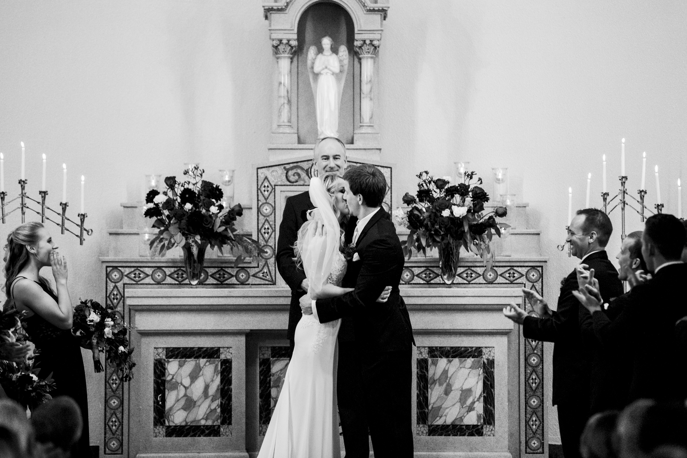 Bride and groom kiss during wedding ceremony in Nazareth Hall