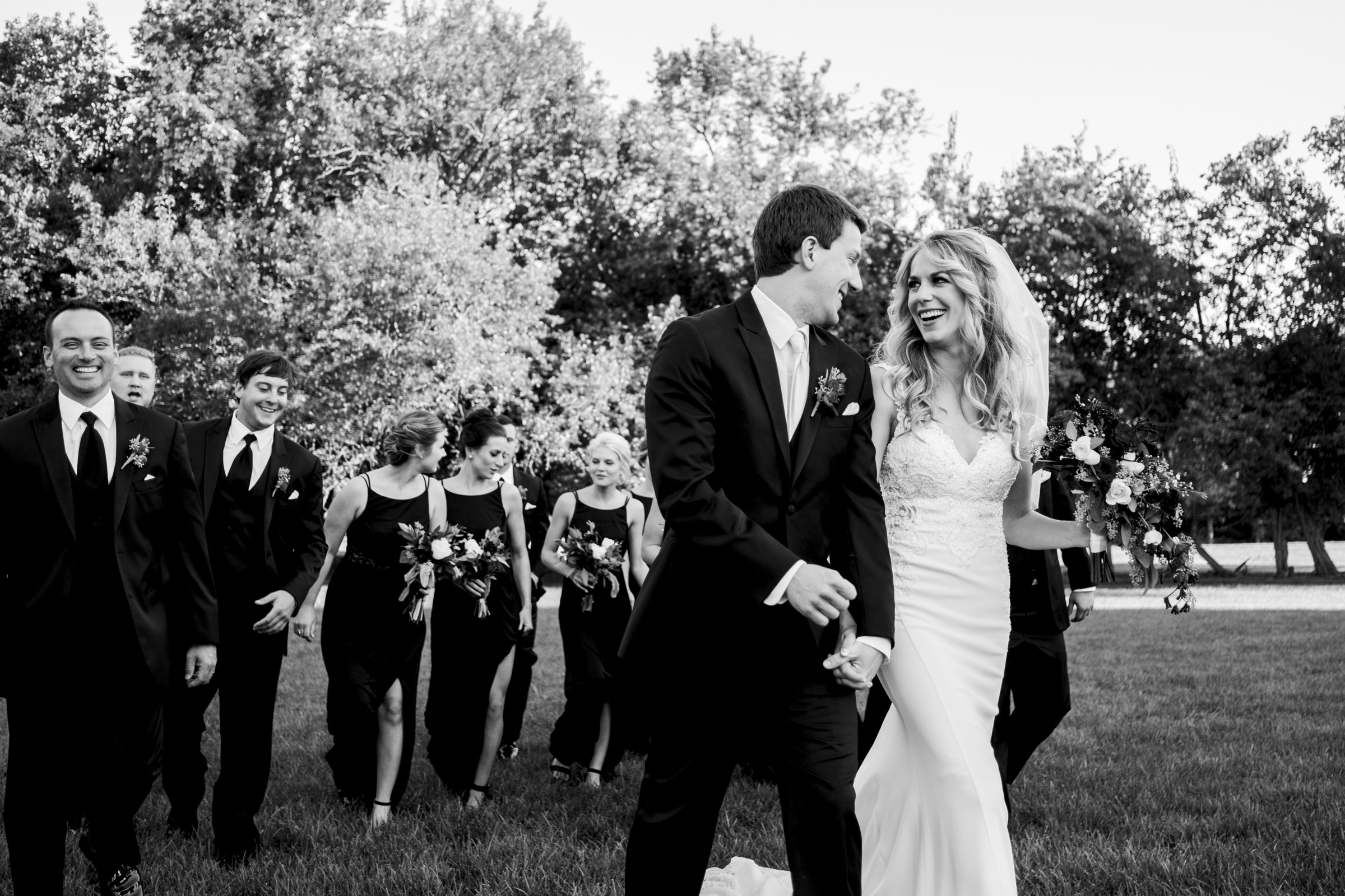Bride and groom walk in black and white with their bridal party through a field