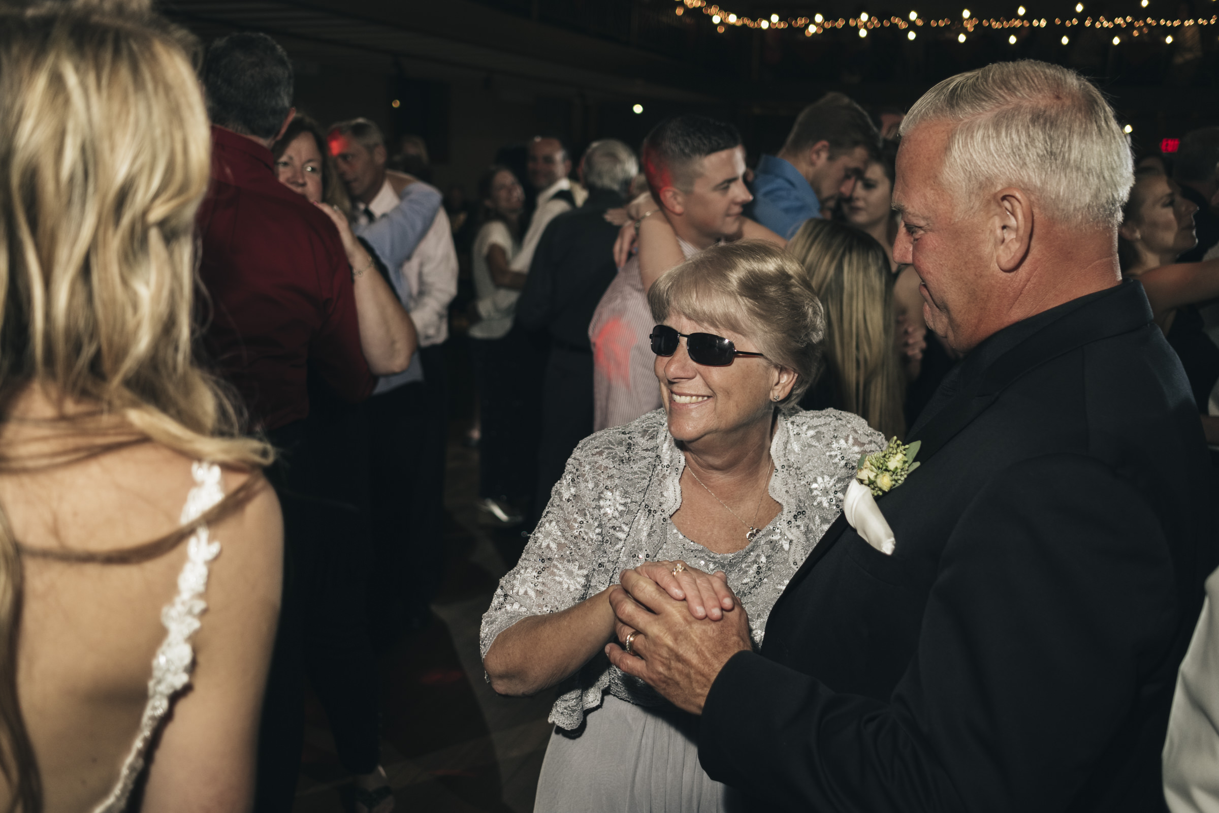 Bride dances with her husband and new in-laws at wedding reception