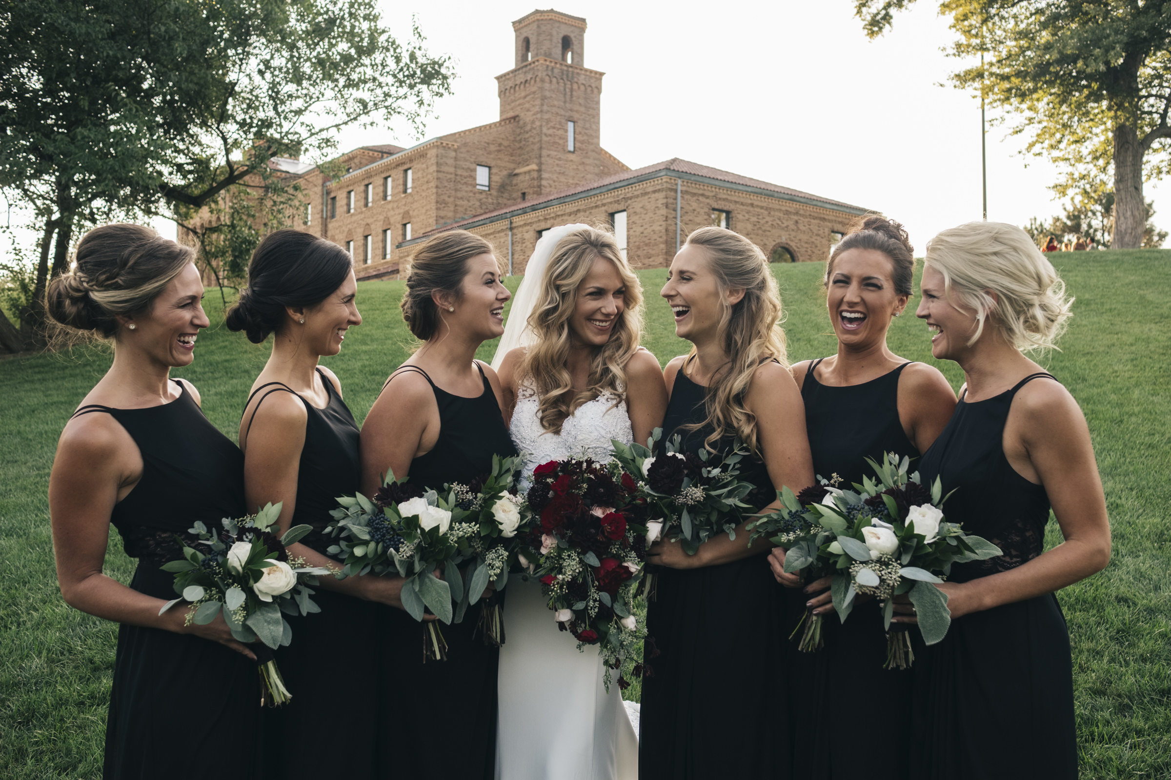 Bridesmaids laugh with the bride during her wedding during in navy blue dresses and beautiful florals
