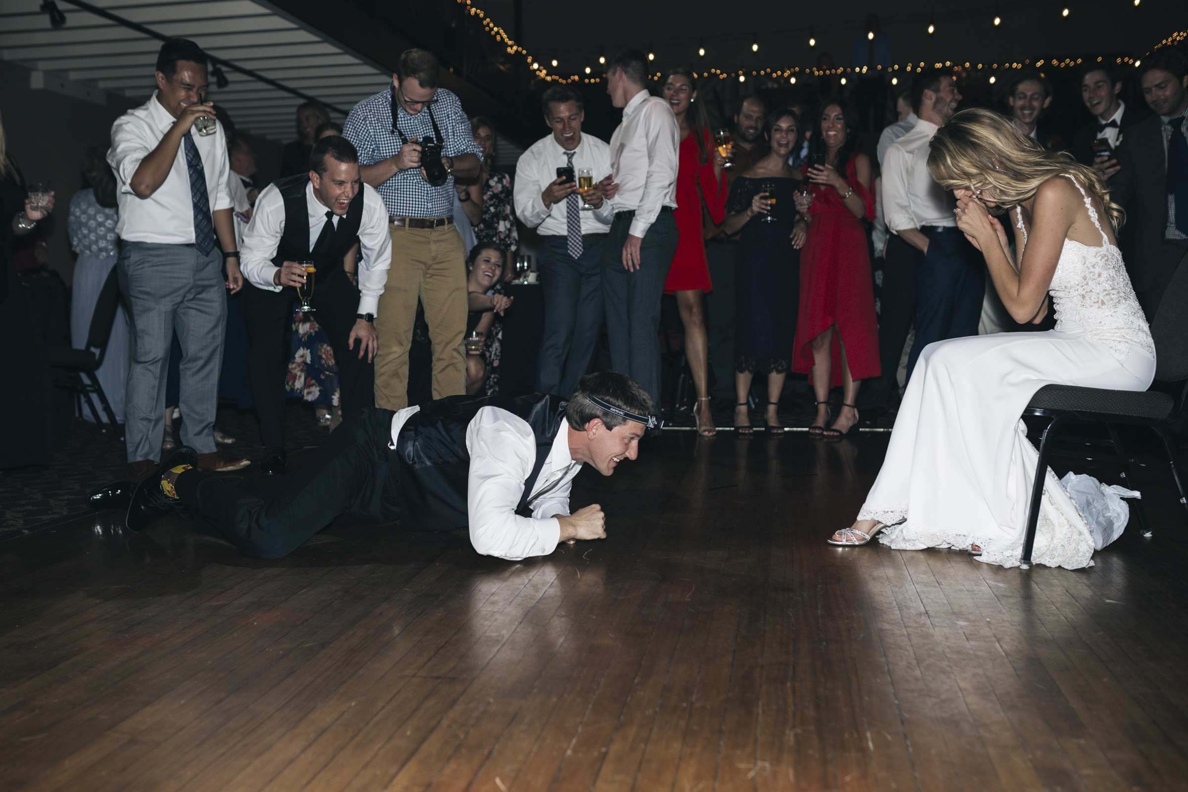 The groom hunts for the garter during wedding reception